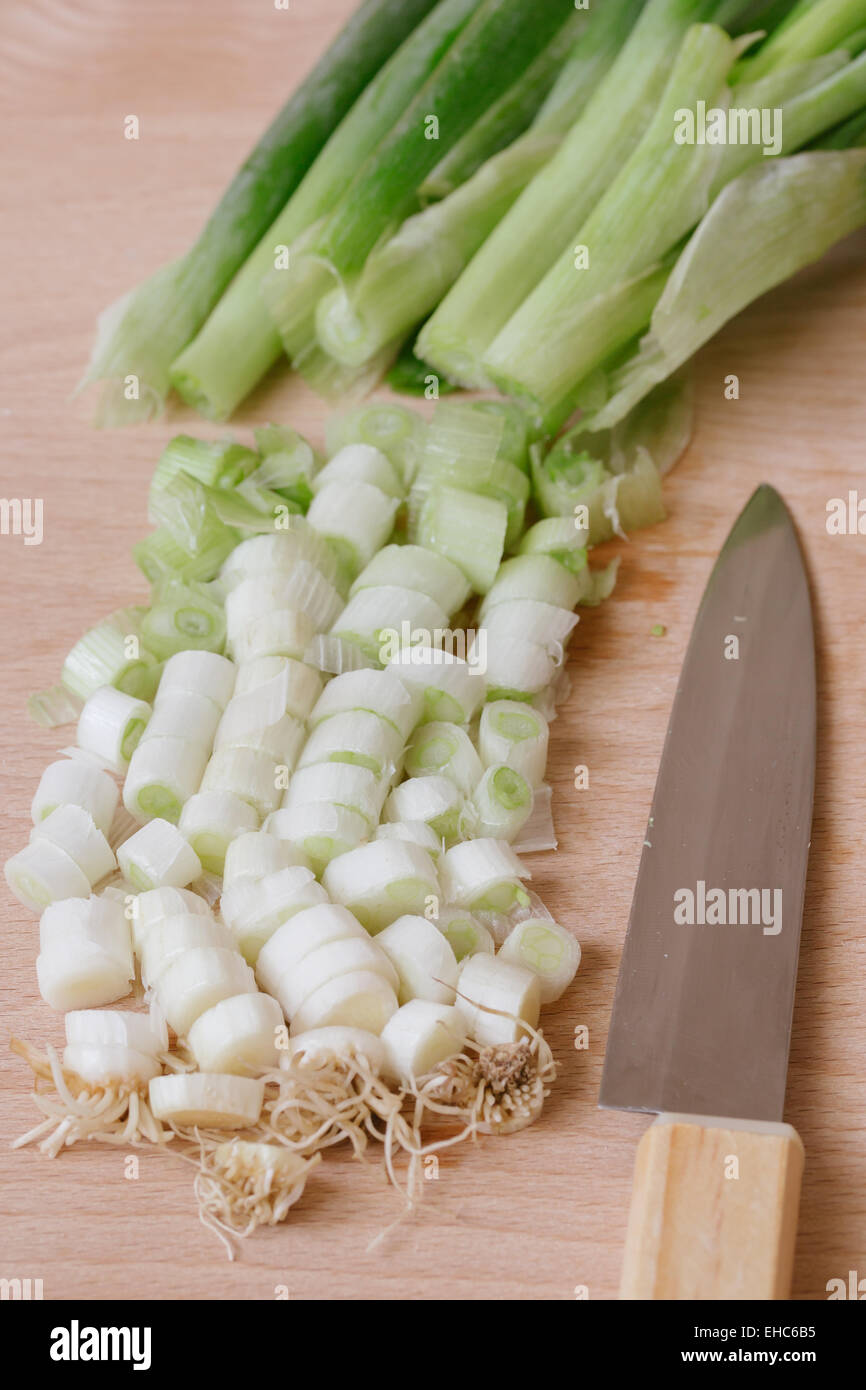 chopped green spring onions on wooden cutting board - Stock Image