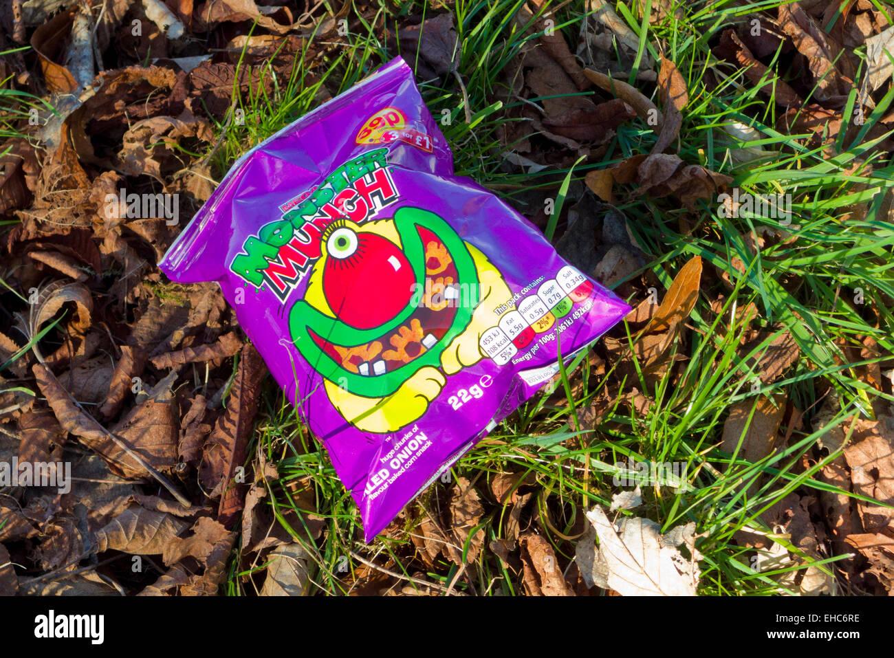 Empty Monster Munch Crisp Packet Littering a Lawn, UK - Stock Image