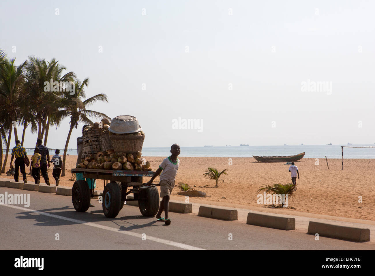 LOME, TOGO, 9th December 2012; A boy pulls a cart of coconuts along the beachfront road. - Stock Image