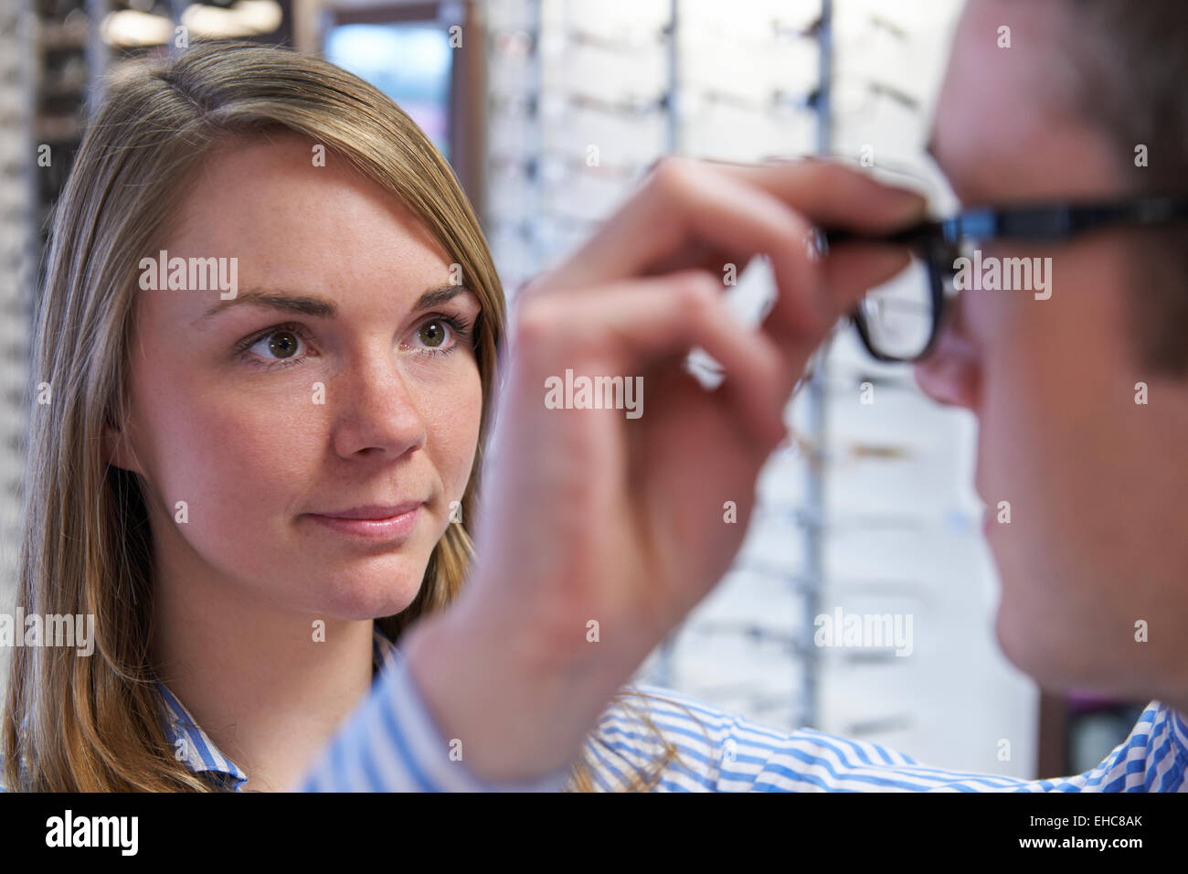 Optician Advising Client On Choice Of Glasses - Stock Image