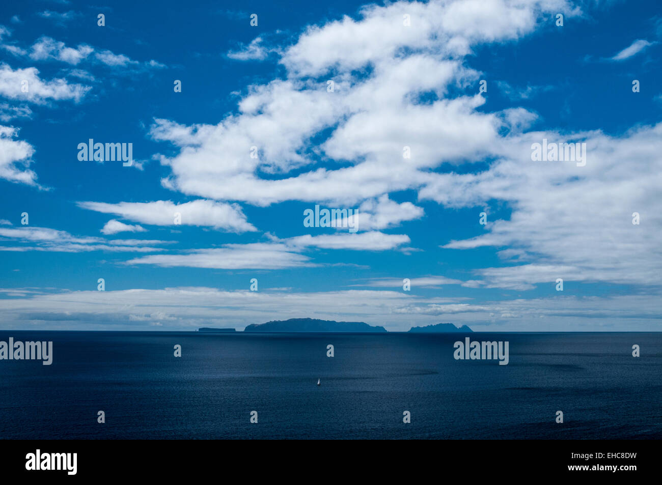 Three desert islands south of Madeira with a yacht barely visible in the foreground. - Stock Image