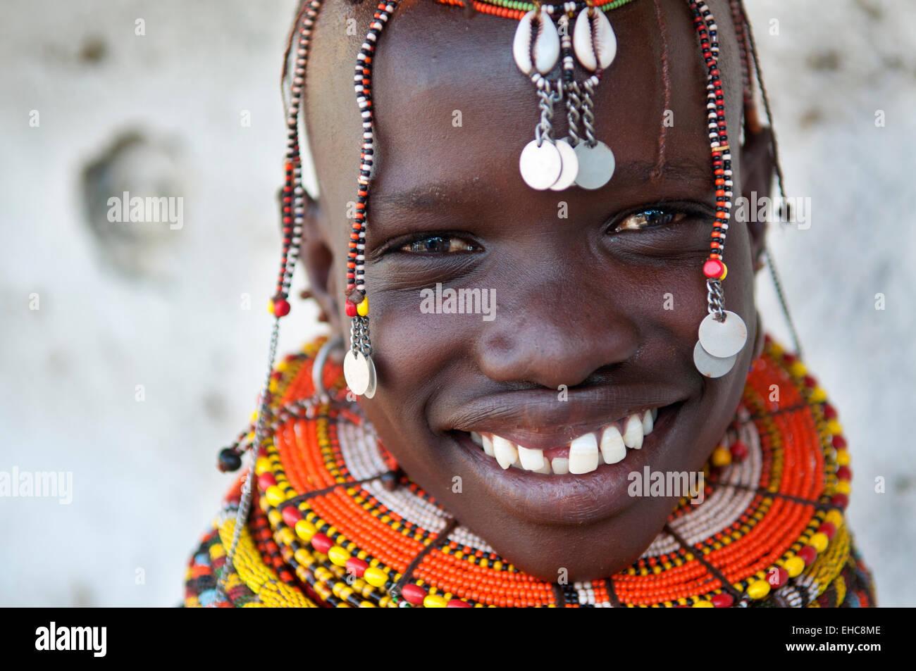 Smiling Turkana girl with massive colorful beaded necklaces and headdress, Loiyangalani, Kenya - Stock Image