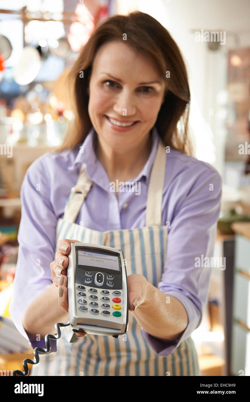 Sales Assistant In Homeware Store With Credit Card Machine - Stock Image