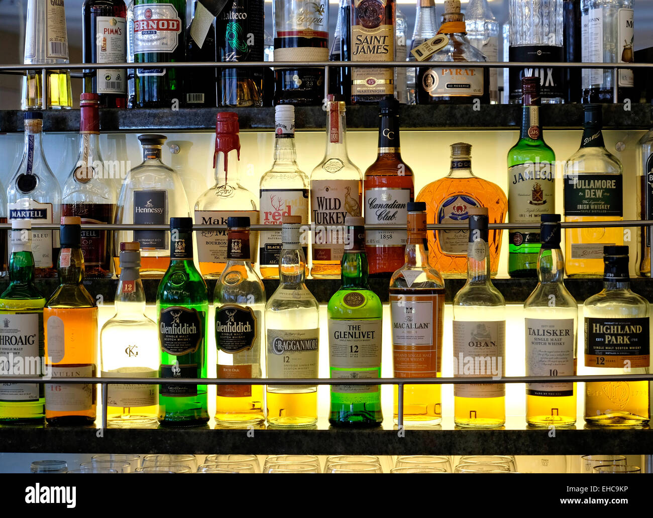 Selection of Whiskeys and other Alcoholic Spirits on a Lit Glass Shelf - Stock Image