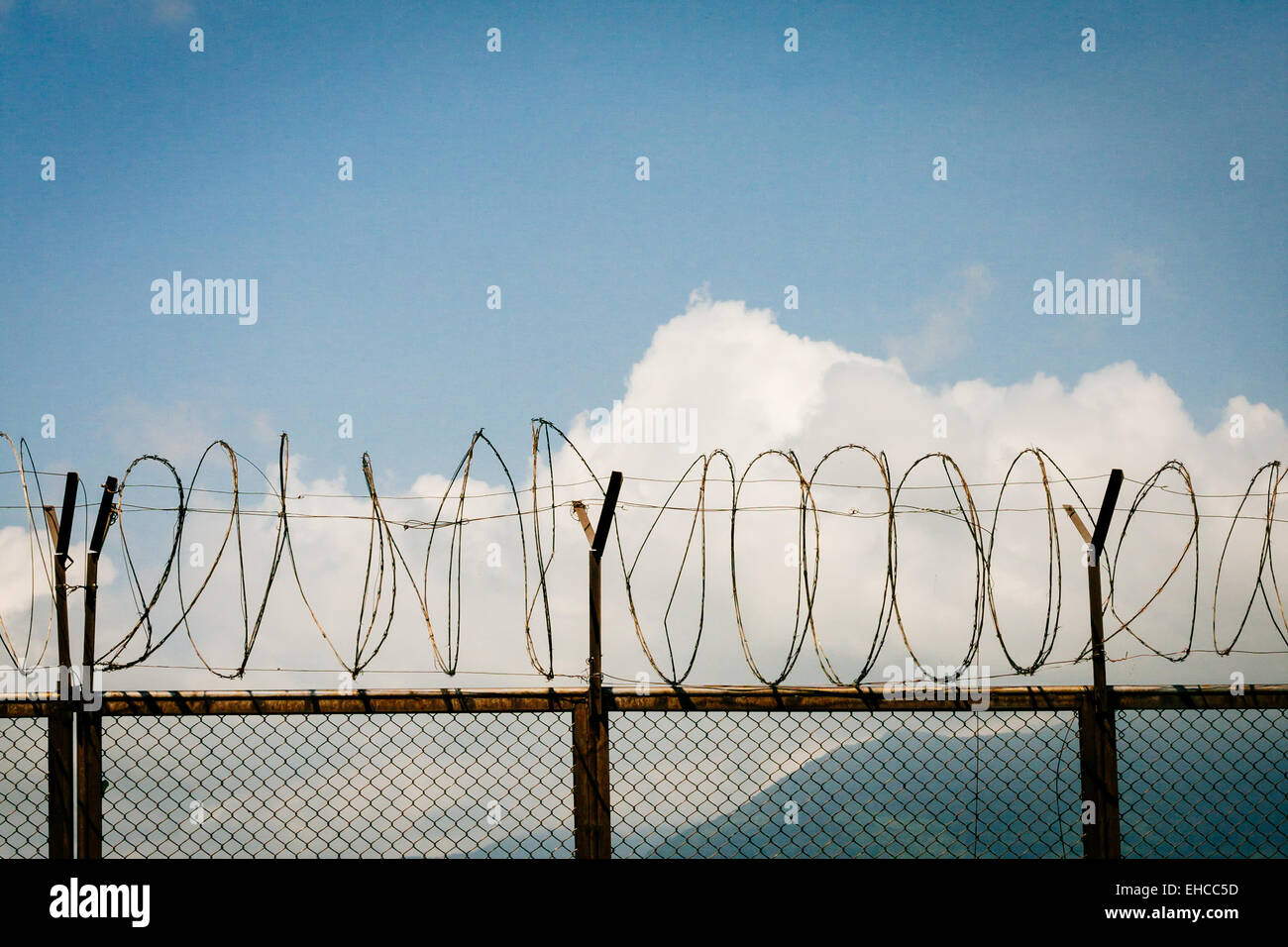 barbed wire fence razor blue sky clouds - Stock Image