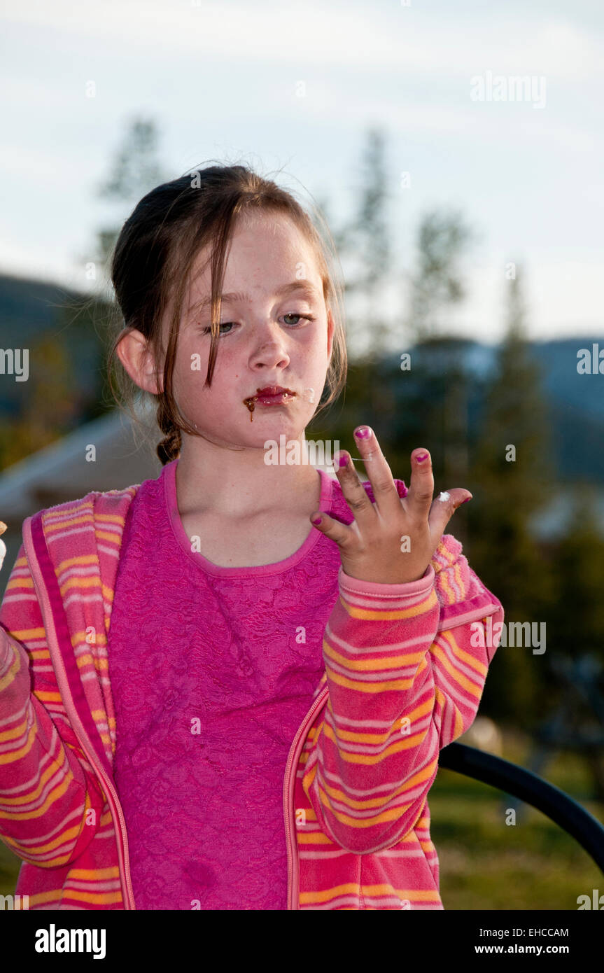 Young girl licking her fingers after eating a s'more (MR) - Stock Image