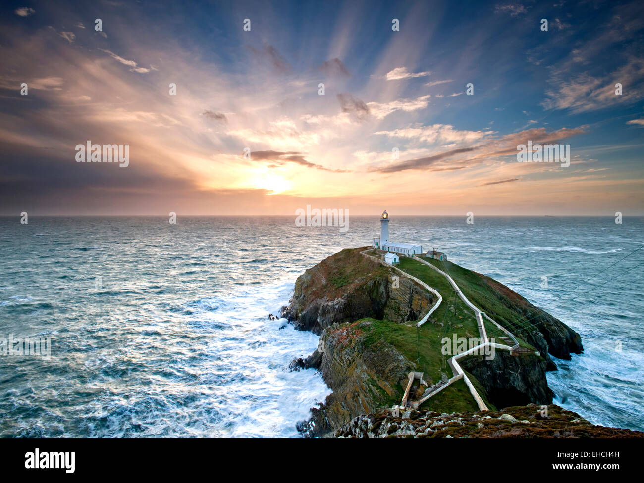 Crepuscular Rays Over South Stack Lighthouse at Sunset, Anglesey, North Wales, UK - Stock Image