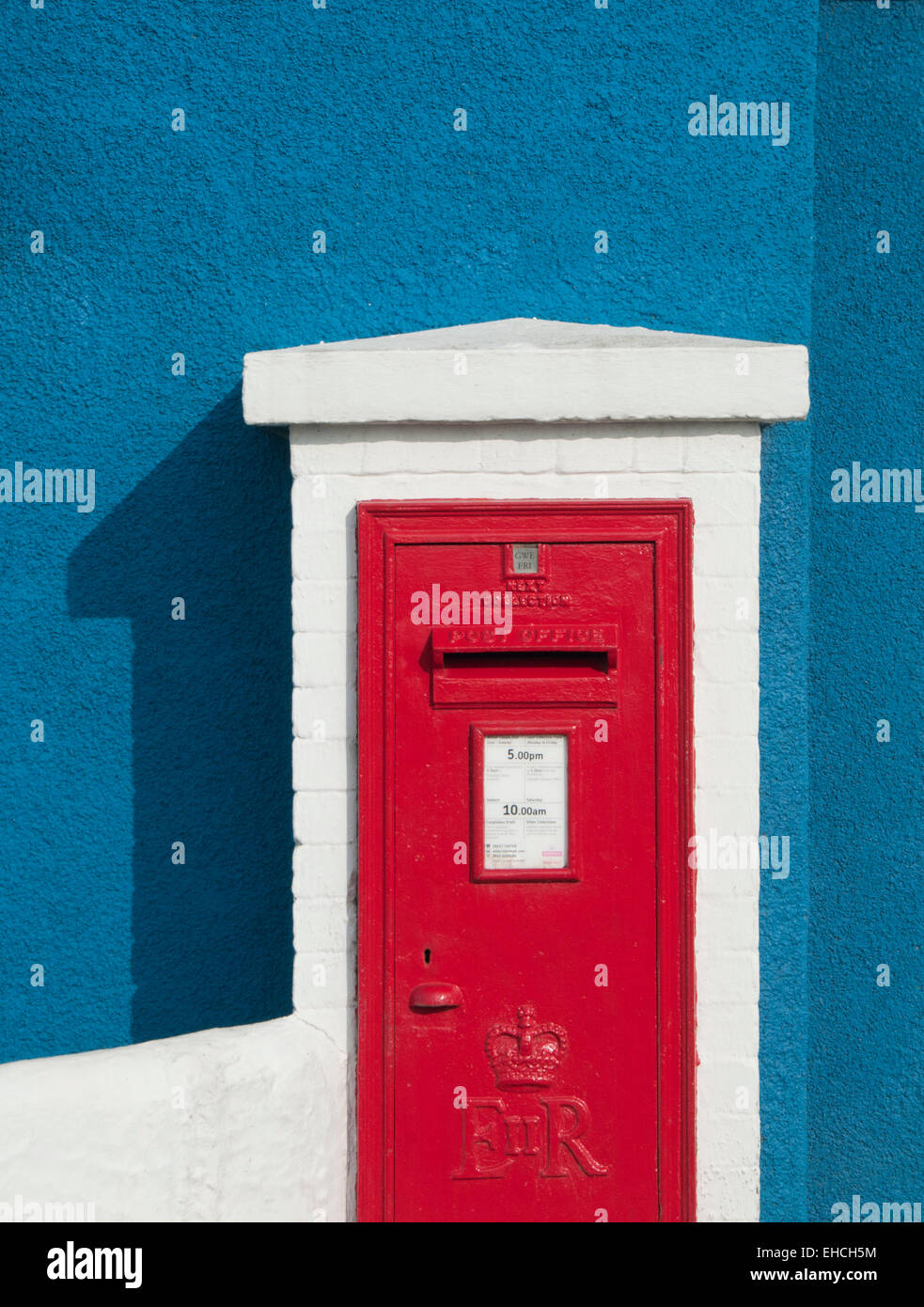 Bright Red Postbox against a Blue Wall, Moelfre, Anglesey, North Wales, UK - Stock Image
