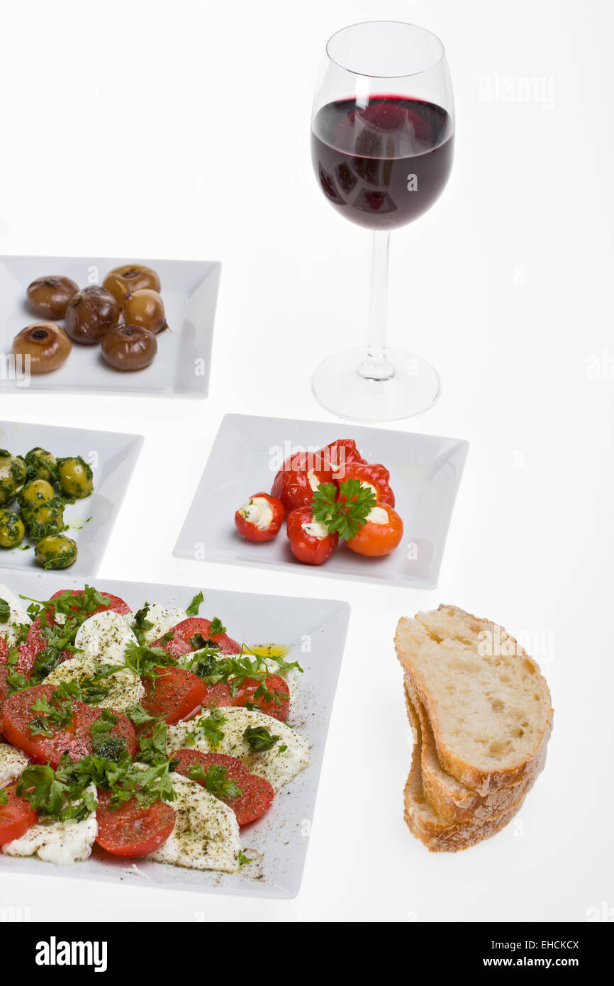 antipasti misti and bread on white plates - Stock Image