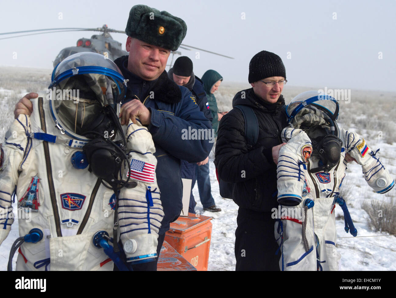 Kazakhstan. 12th March, 2015. People carry space suits of the ISS Expedition 41/42 crew members after the landing - Stock Image