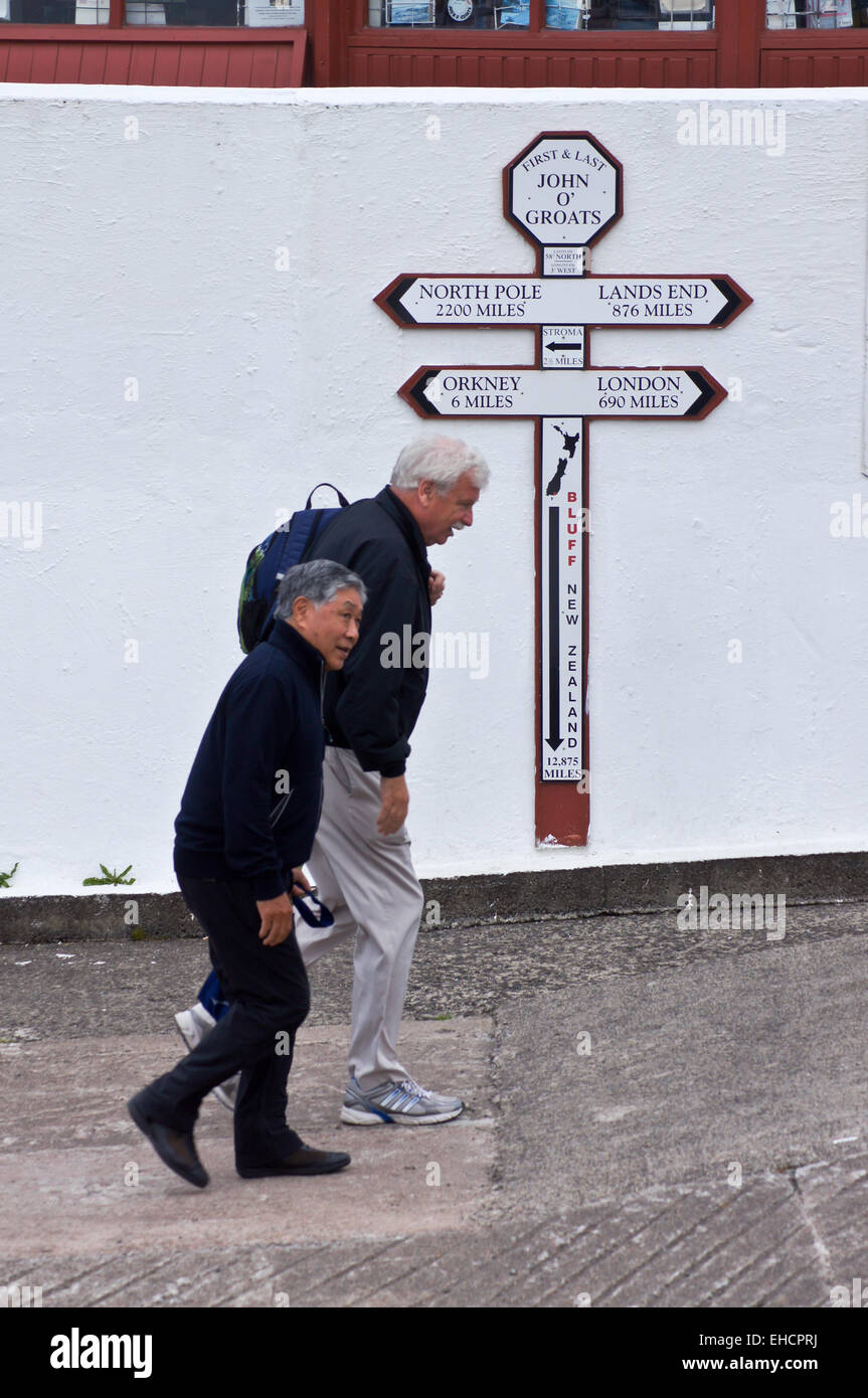 Walkers passing the sign showing distances to Land's End, John O'Groats, Caithness, Scotland Stock Photo