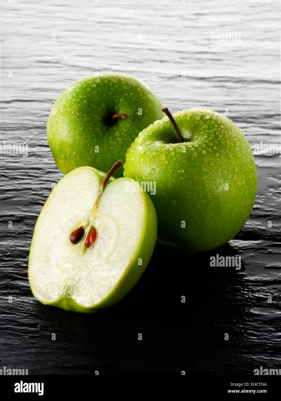 Whole & cut Granny Smith apples - Stock Image