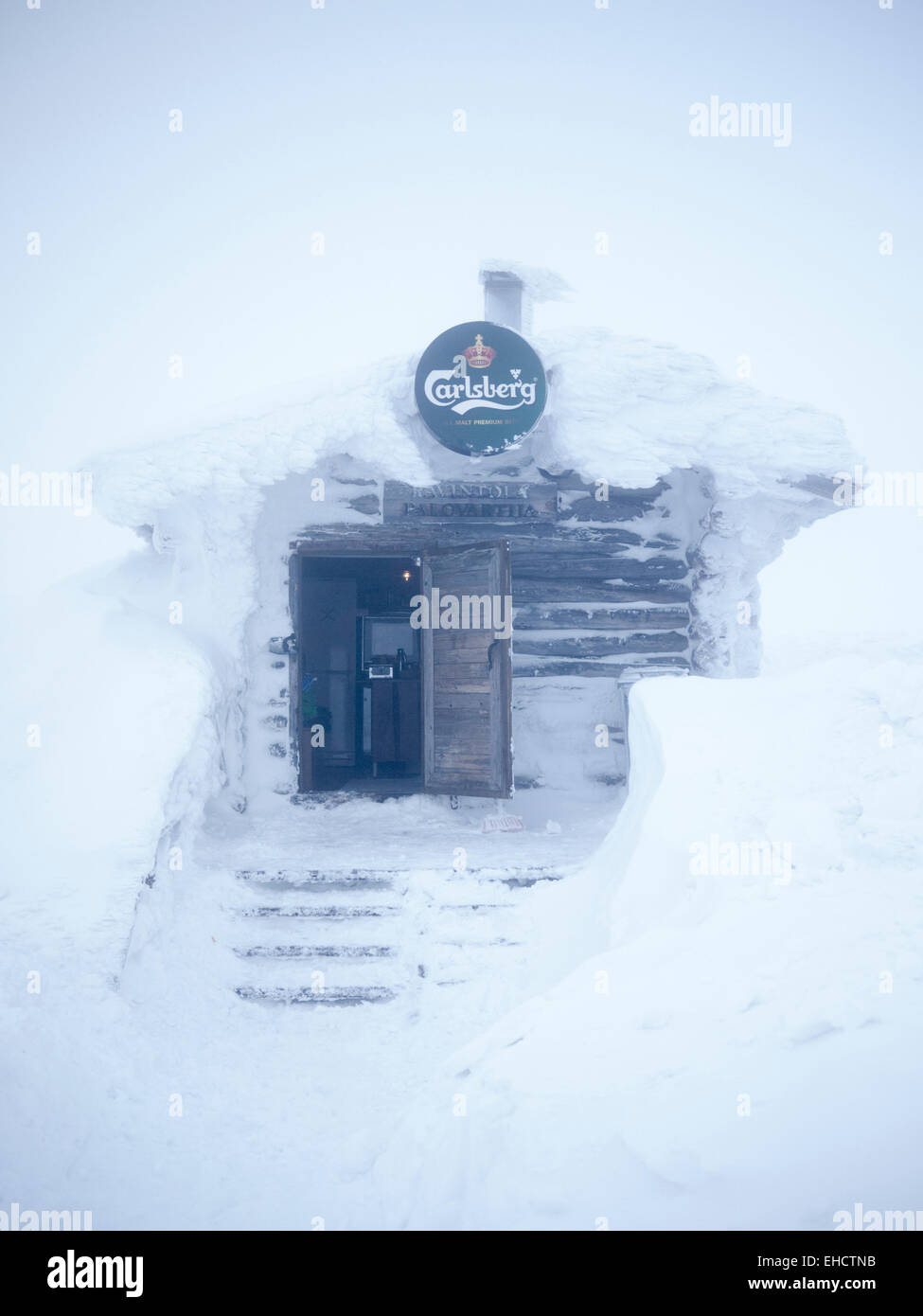 A small log cabin mountain restaurant on the piste at the ski resort of Levi, Lapland Finland with a Carlsberg sign - Stock Image