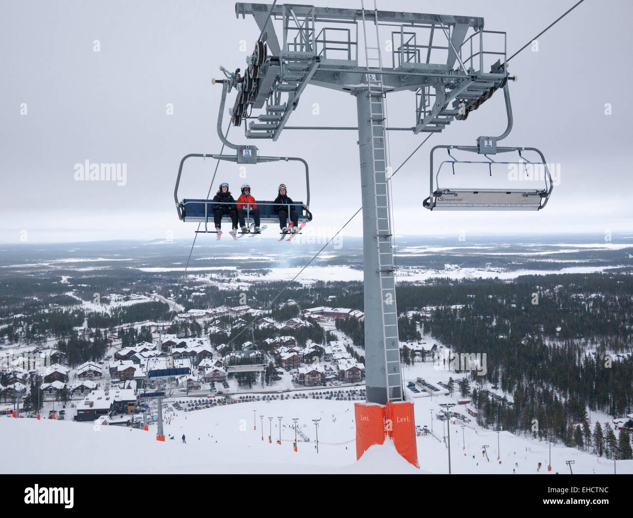 A chairlift carrying skiers up the mountain at the ski resort of levi, Lapland Finland in grey overcast conditions - Stock Image