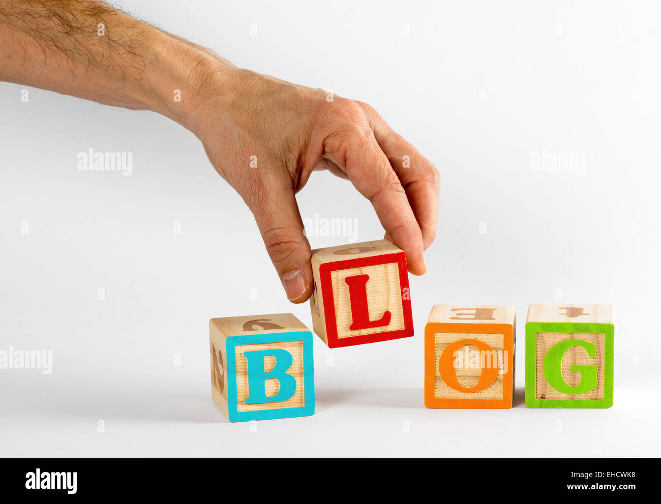 Male Hand Spelling the Word Blog with Colorful Children Blocks on White Background - Stock Image