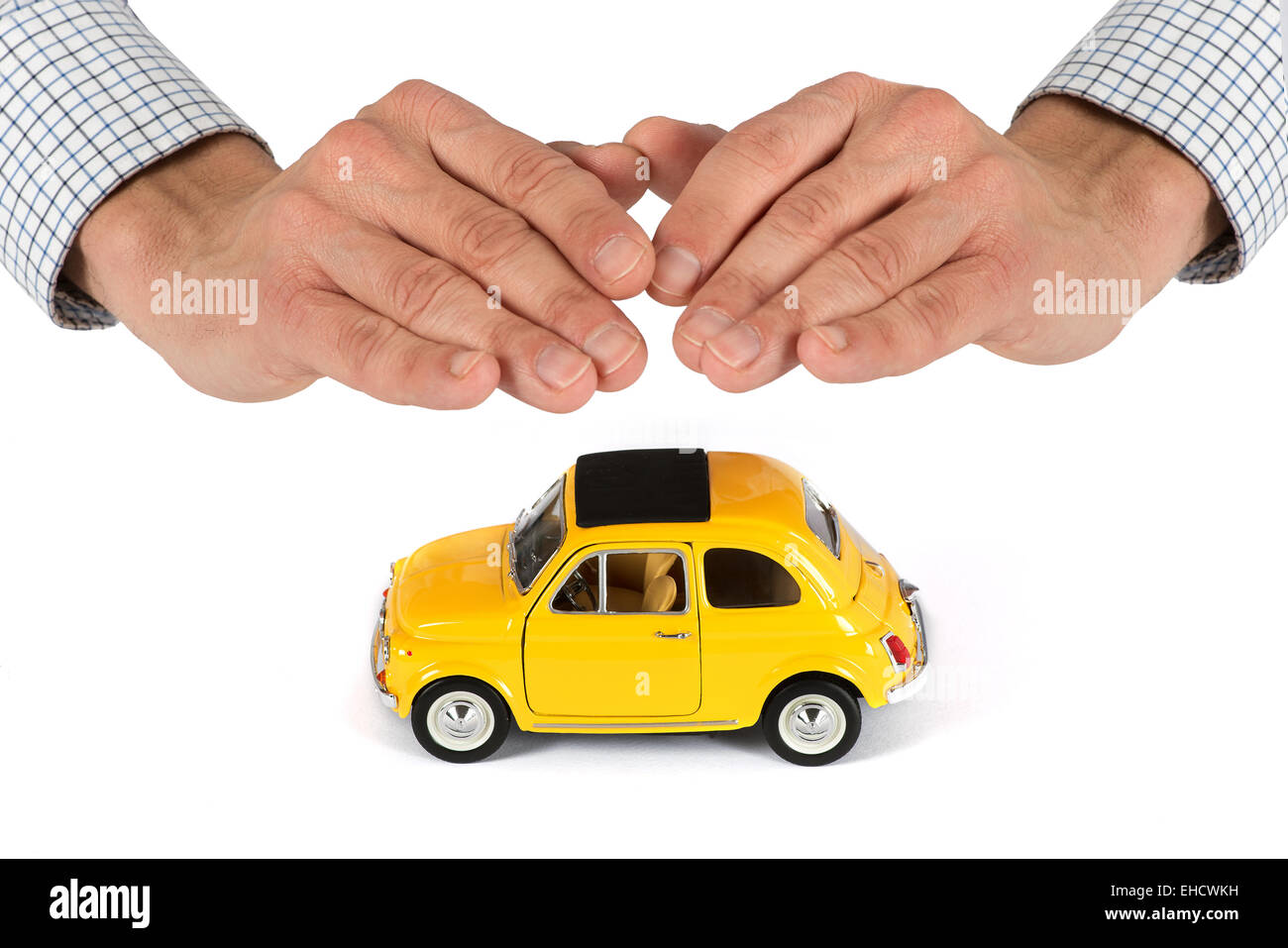 Adult Male Hands Providing Protective Cover Over Top of Yellow Toy Car, Insurance Concept Image - Stock Image