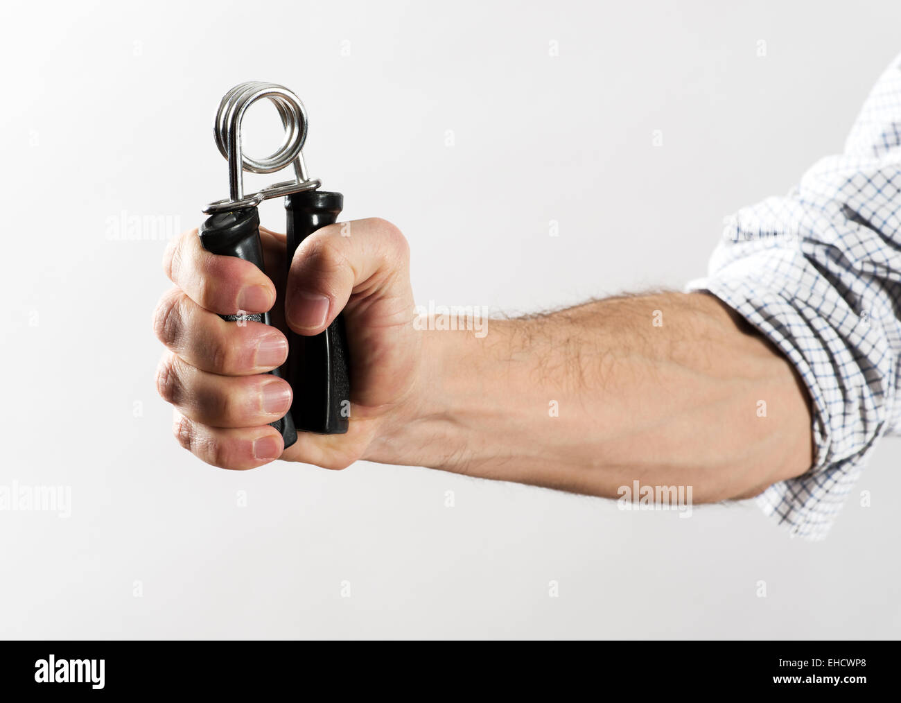 Male Hand with Rolled Up Shirt Sleeve Exercising Strength Using Hand Gripper Against White Background - Stock Image