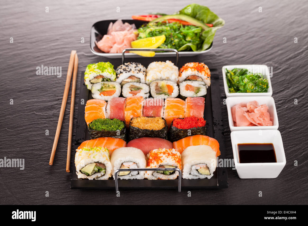 Delicious sushi rolls served on black plate and stone - Stock Image