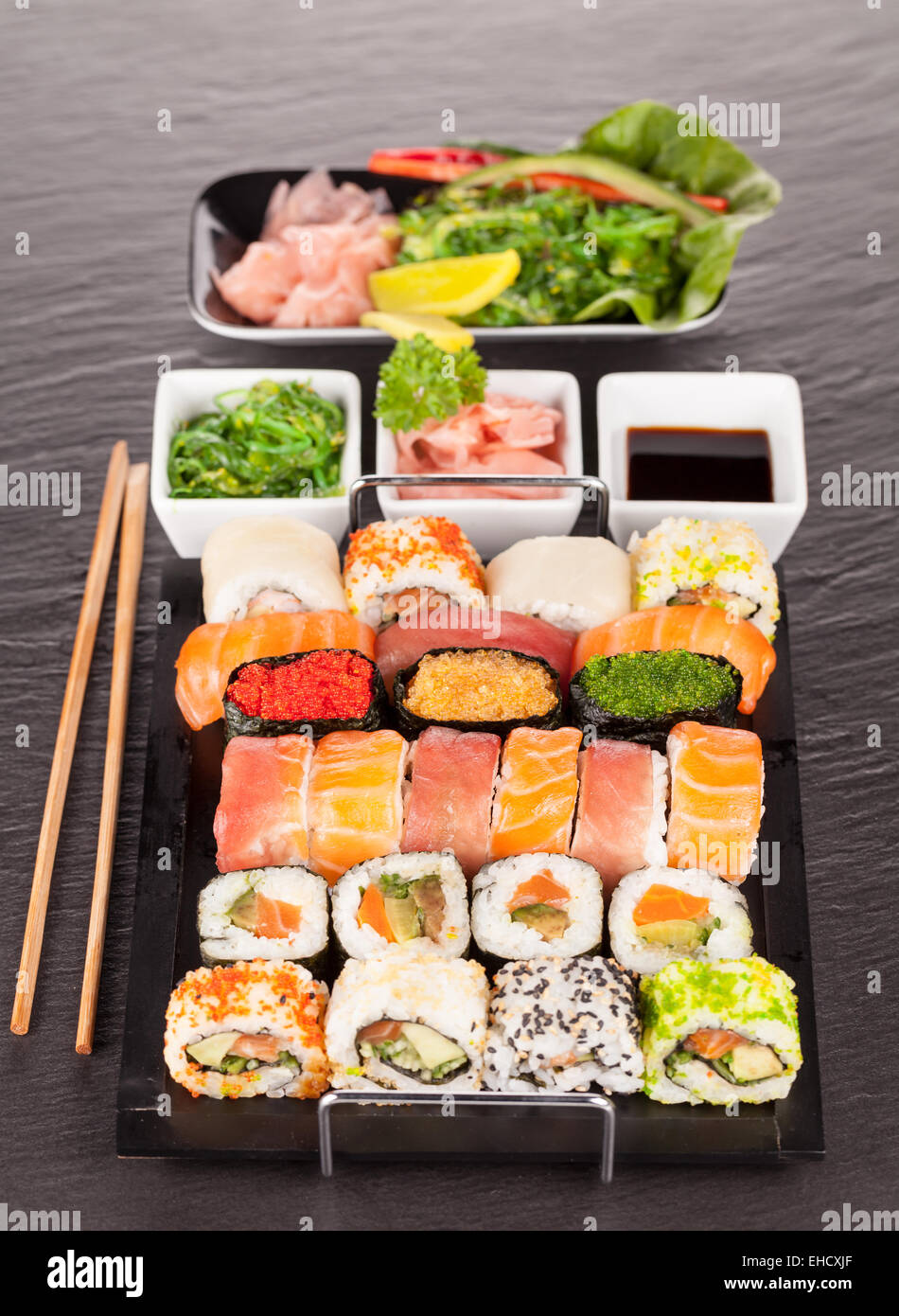Delicious sushi rolls served on black plate and stone Stock Photo