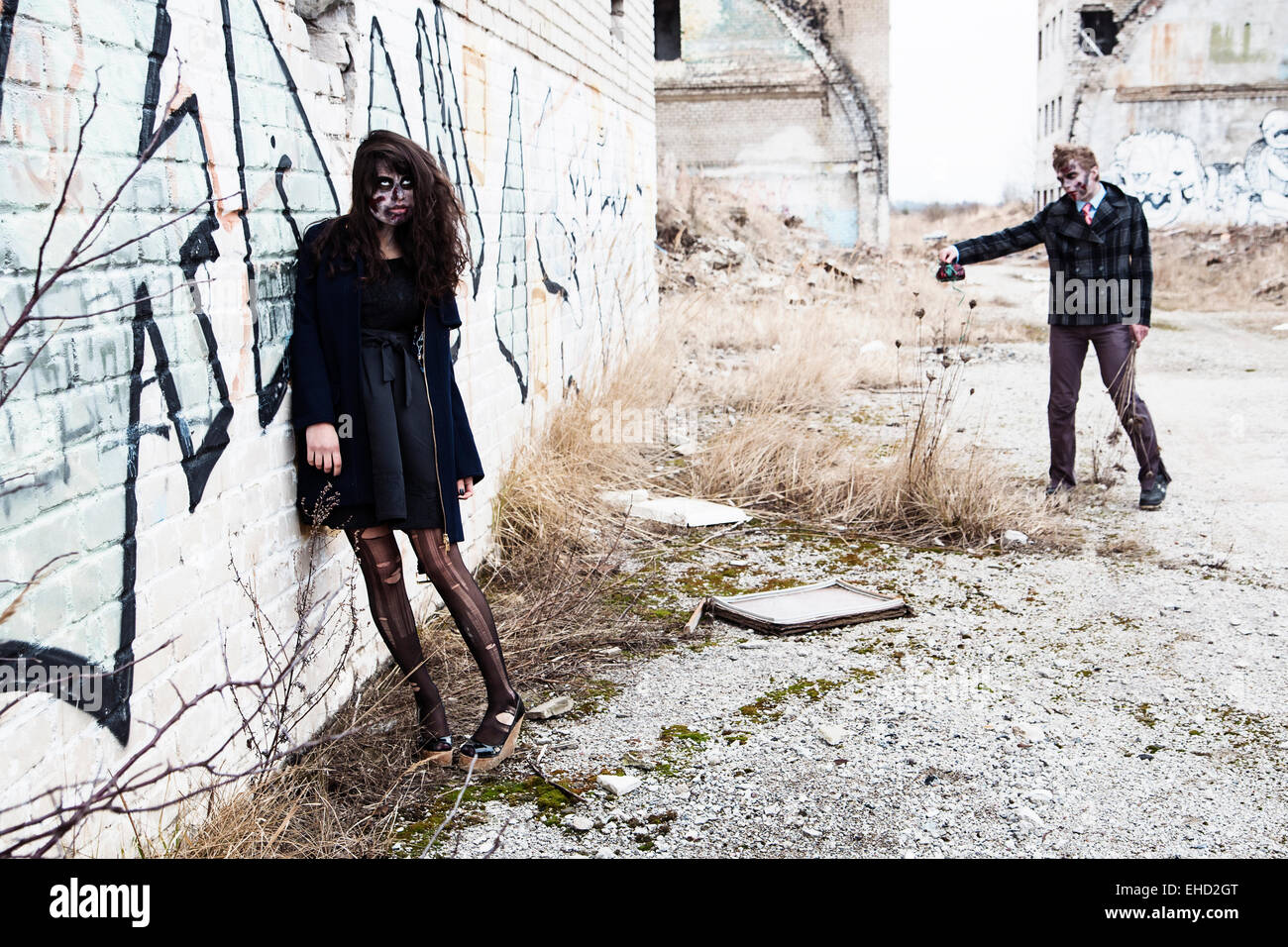 Young woman standing neat the crepy wall - Stock Image