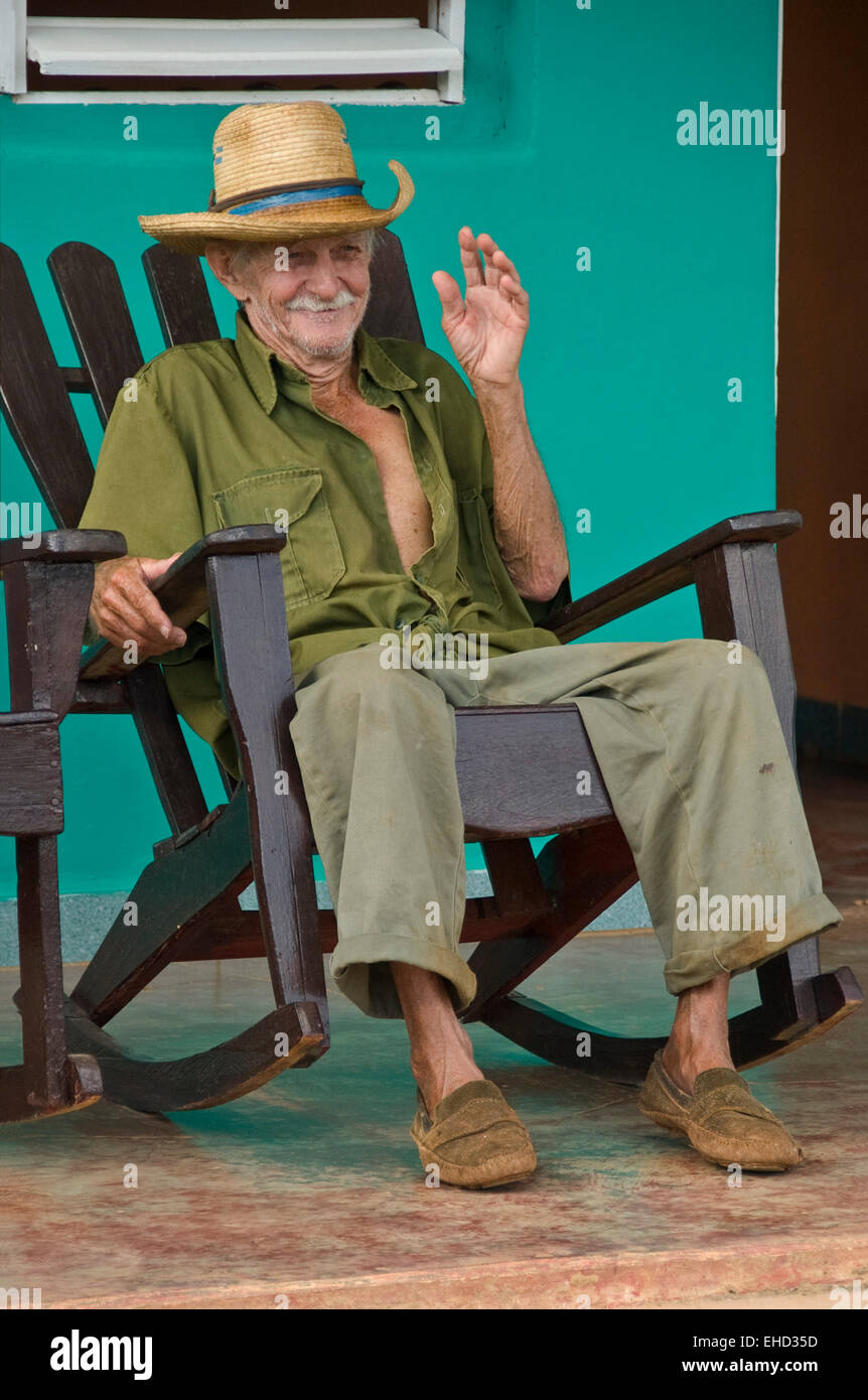 Vertical View Of An Old Cuban Man Sitting On His Veranda In A