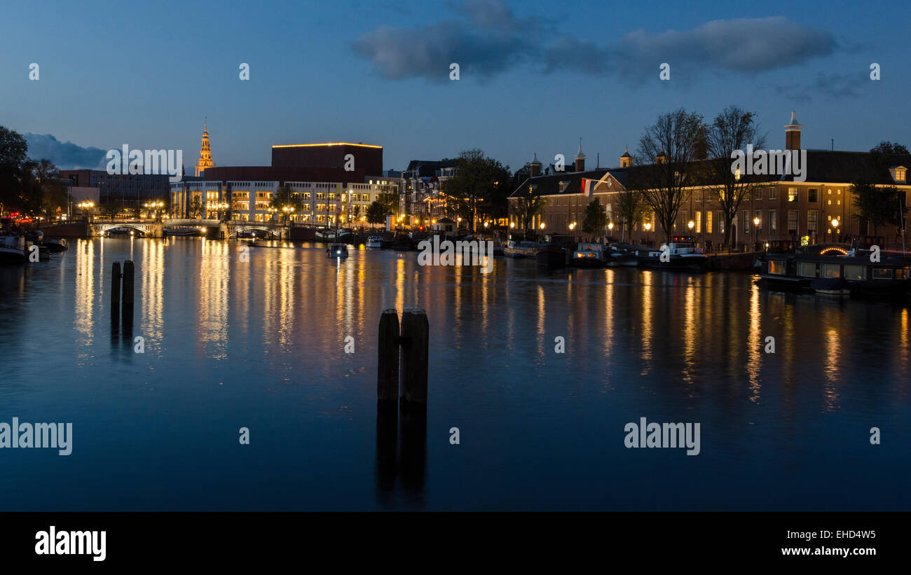 A view of the river Amstel in Amsterdam after the sun has set and the sky is a deep blue. The city's skyline - Stock Image