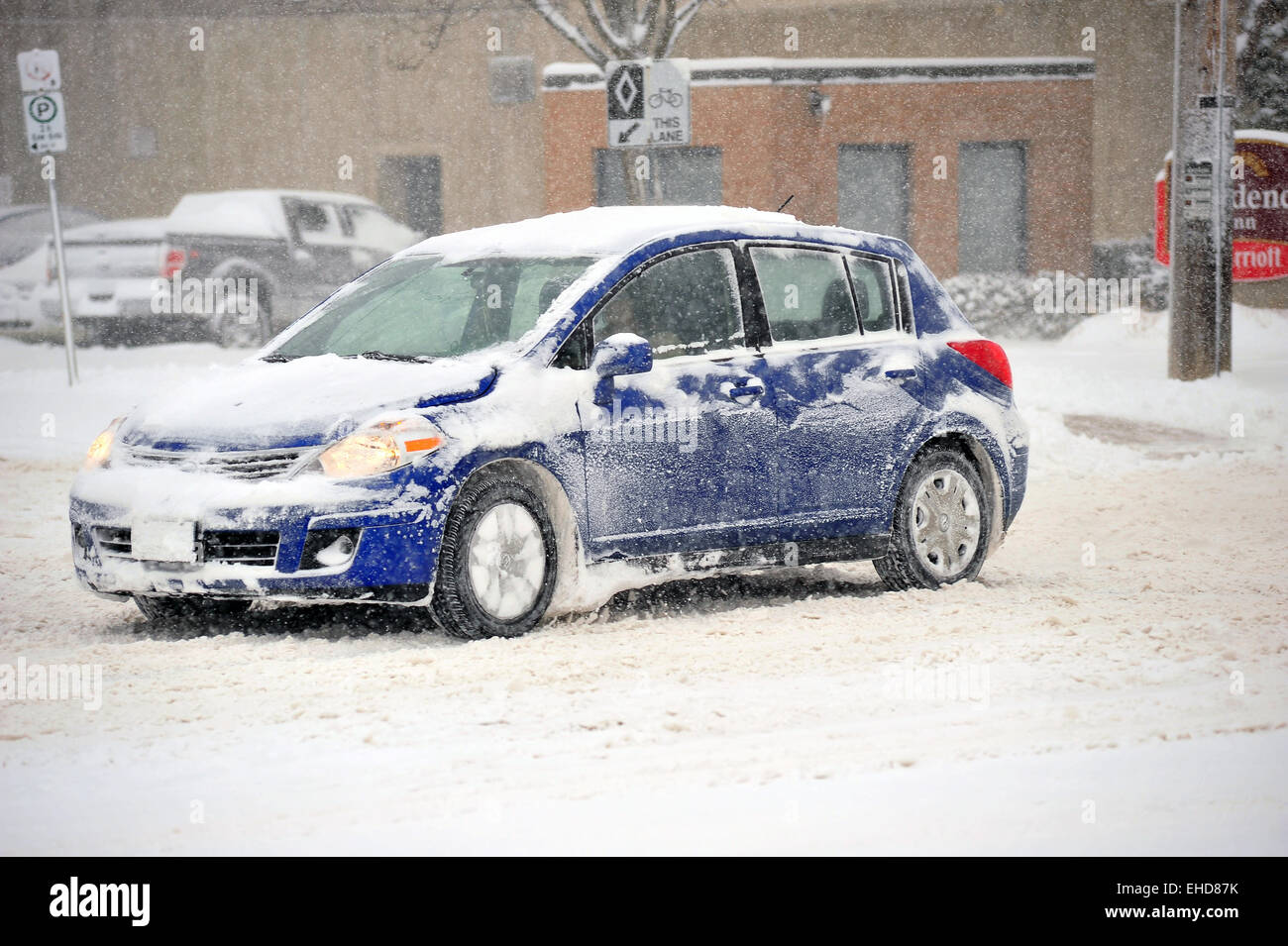 A cars spins its' front wheel driving on snowy roads in Canada. - Stock Image