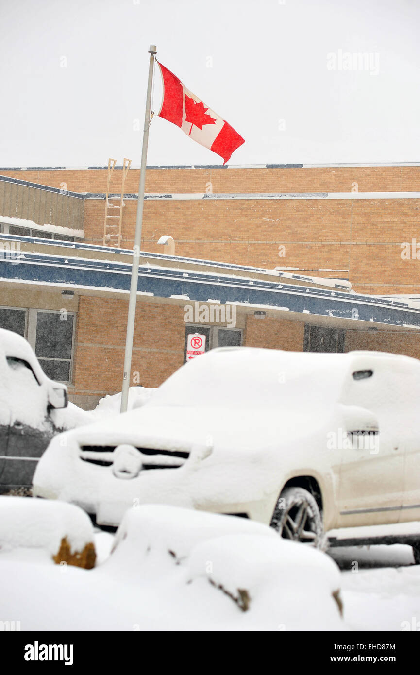 A Canadian flag blows in the wind above snow covered cars in a car park in London, Ontario. - Stock Image