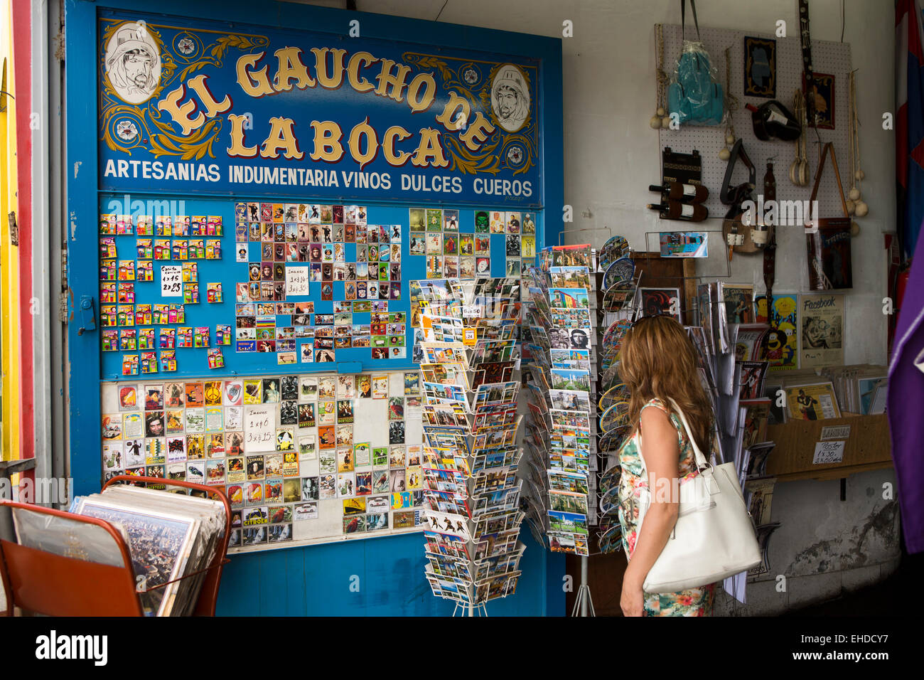 Argentina, Buenos Aires, La Boca, Magallenes, woman in souvenir shop browsing postcards - Stock Image