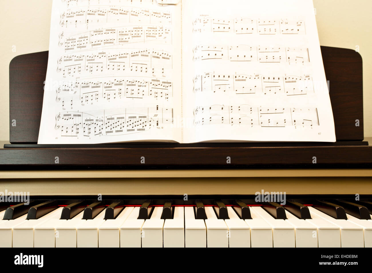 Piano keys and music paper close-up - Stock Image
