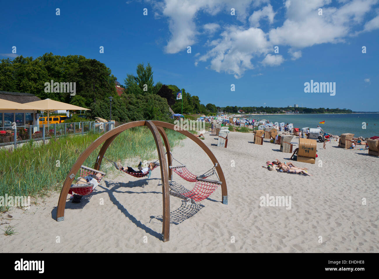 Sunbathers in hammocks and beach chairs at the seaside resort Haffkrug, Schleswig-Holstein, Germany - Stock Image