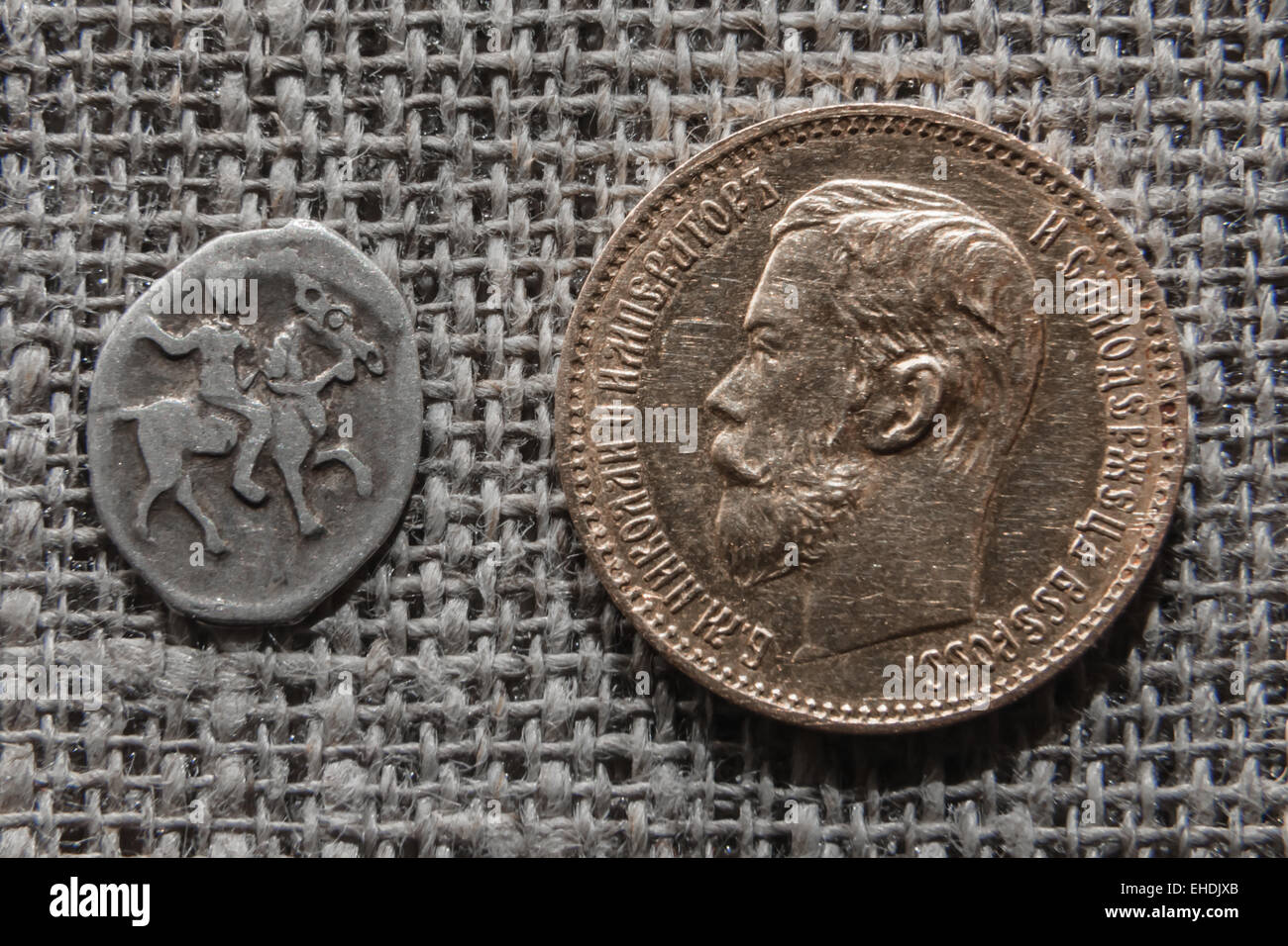 Evolution of the Russian money - silver Moscow kopek of Ivan Grozny and gold 5 rubles of Nikolay Romanov - Stock Image