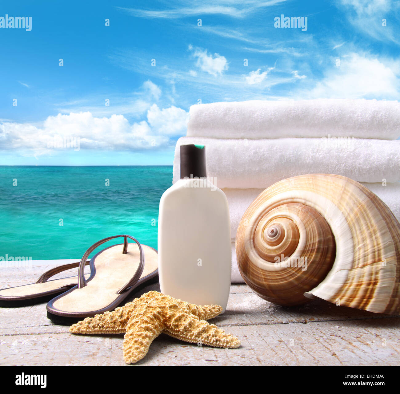 Sunblock lotion and towels and ocean scene - Stock Image