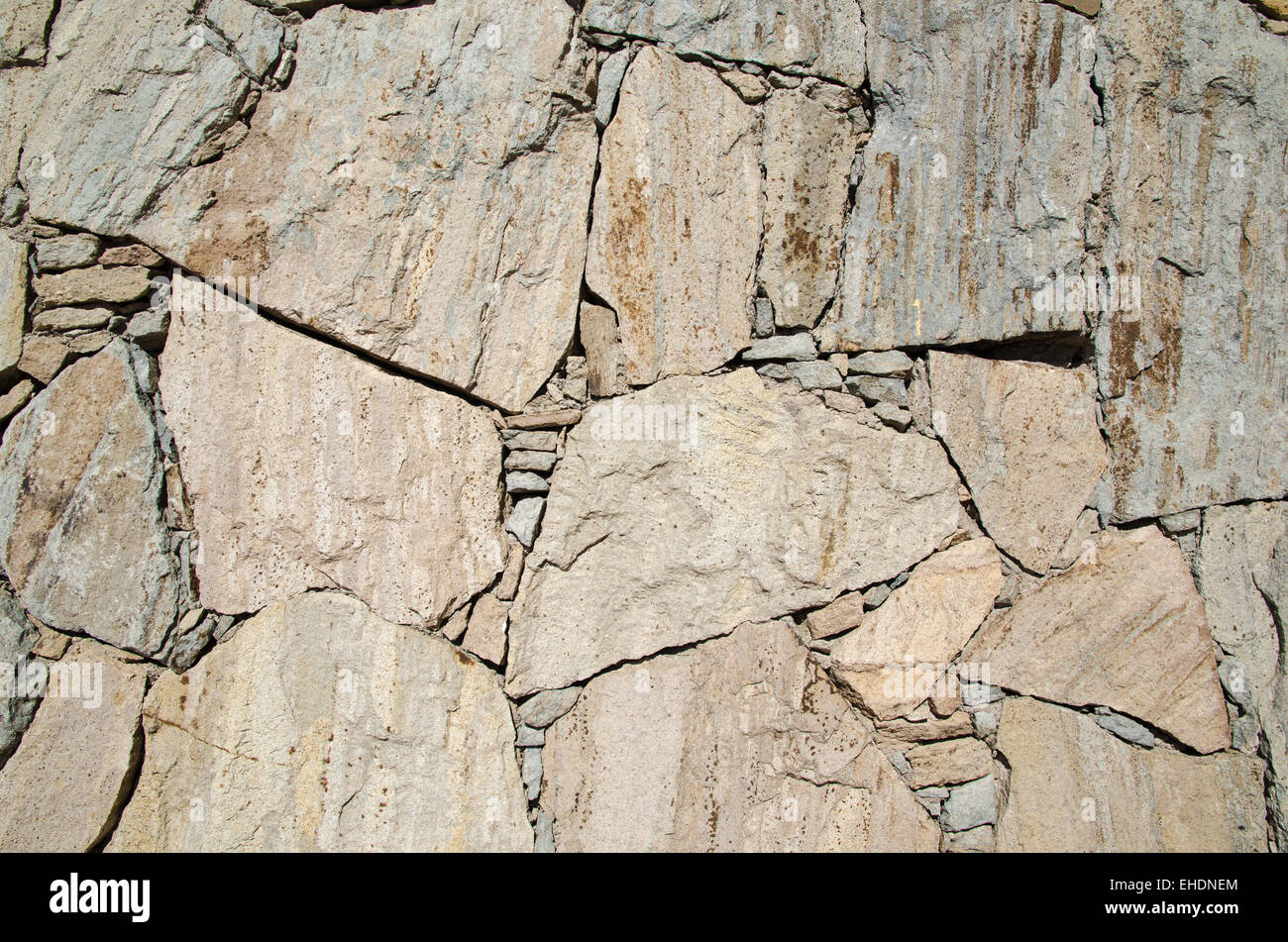 Bright sunlit stone wall background - Stock Image