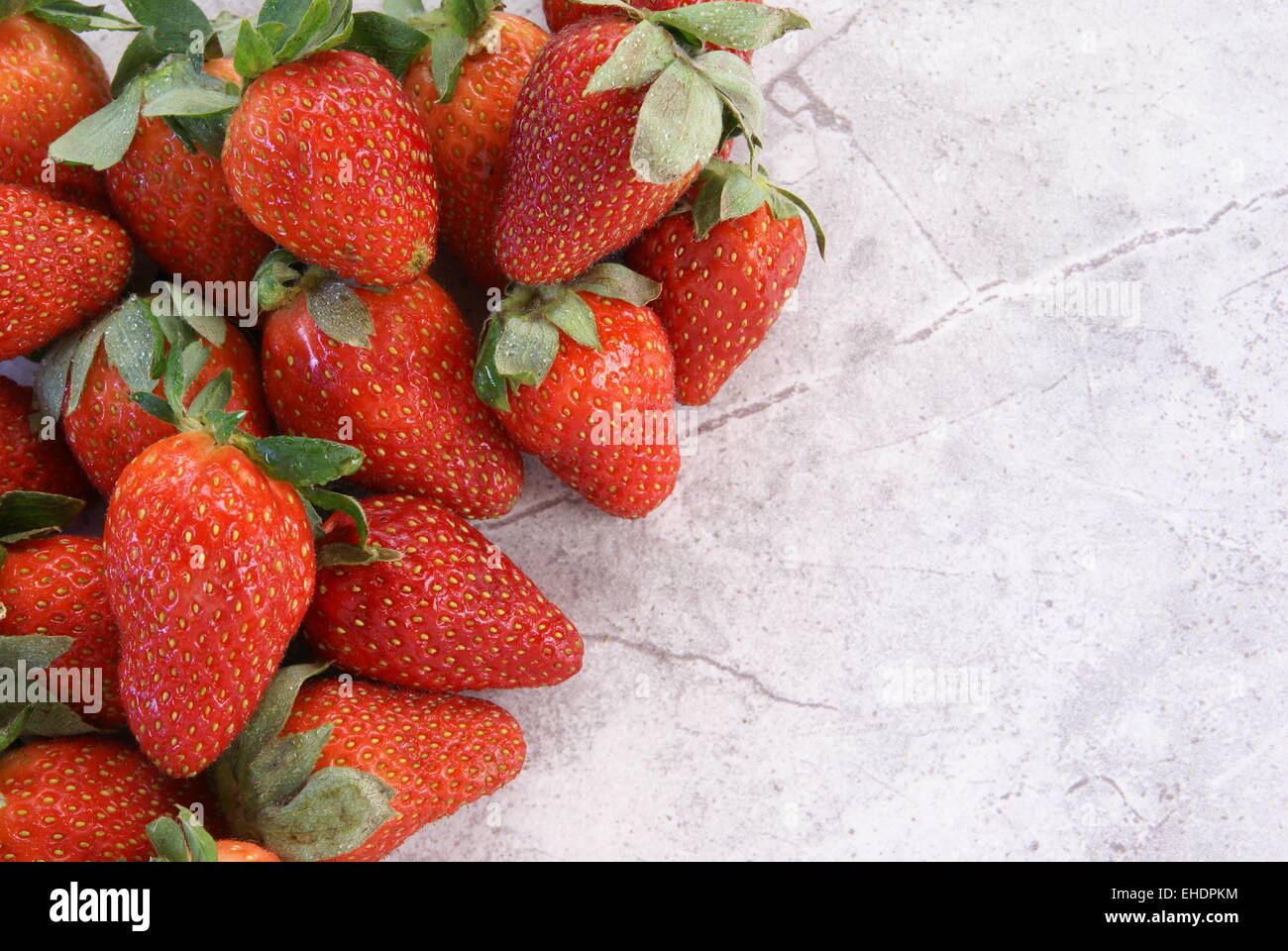 Strawberries are piled to the left and top on a marble counter or tabletop with a top down view and plenty of room - Stock Image
