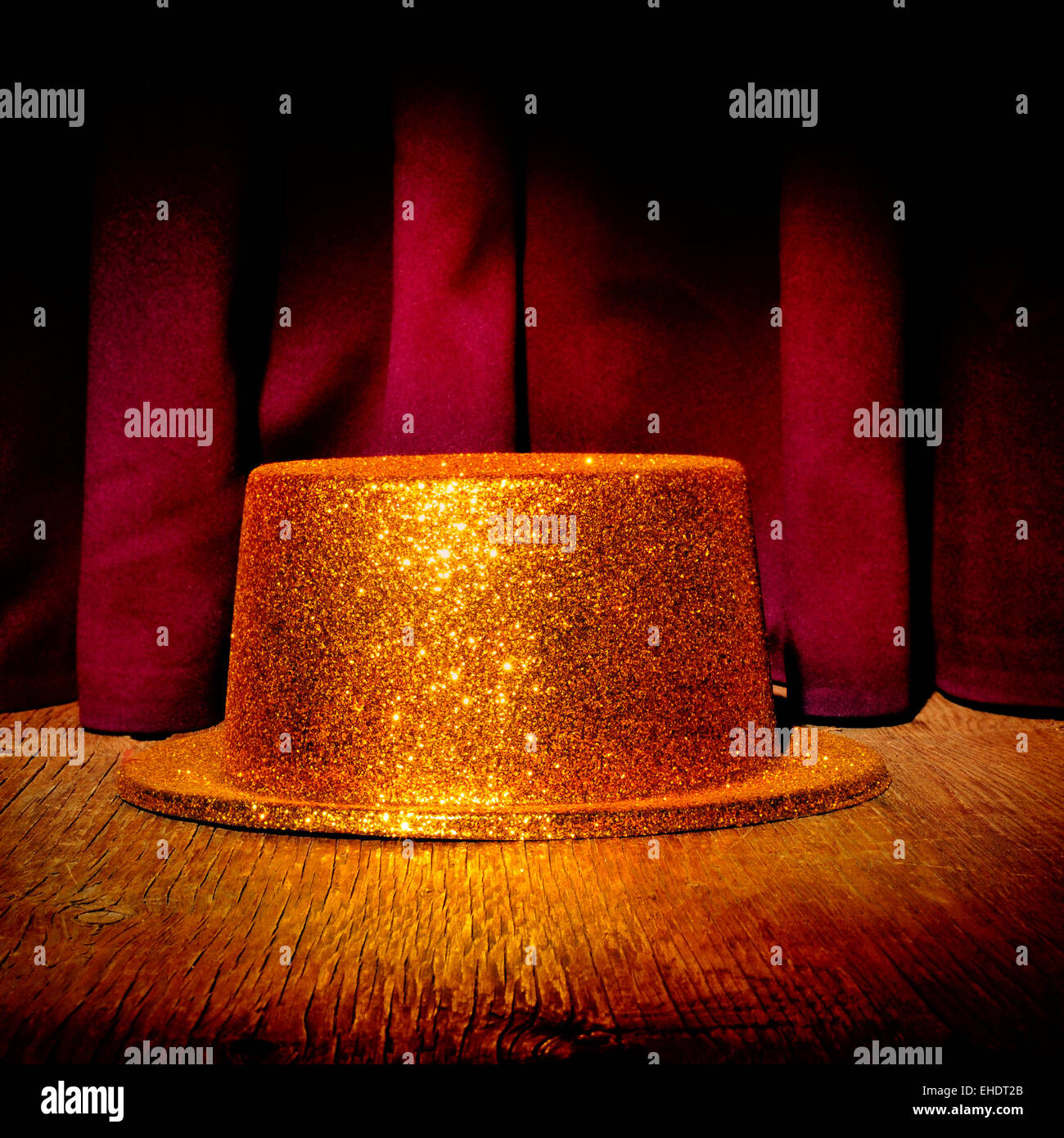 a golden top hat on a stage with the theater curtain in the background - Stock Image