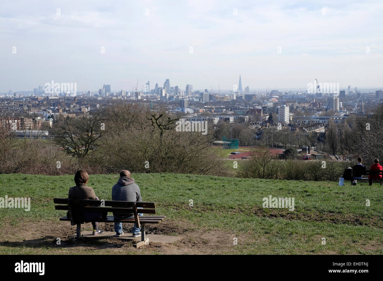 A rear view of two people sitting on a bench in Hampstead Heath - Stock Image