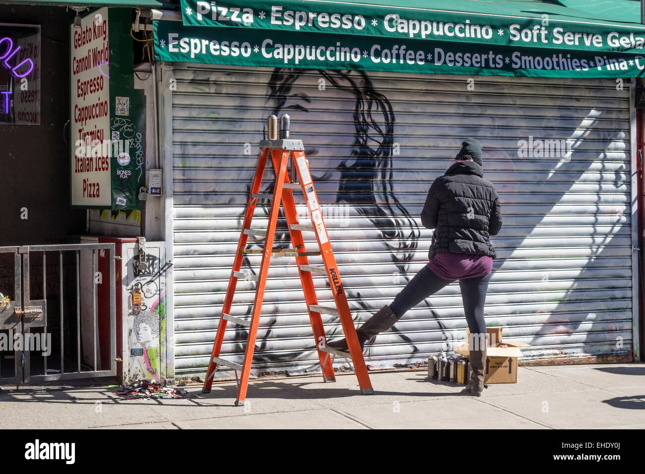 Spray paint mural artist painting a picture of a woman on a store in Little Italy in New York City - Stock Image
