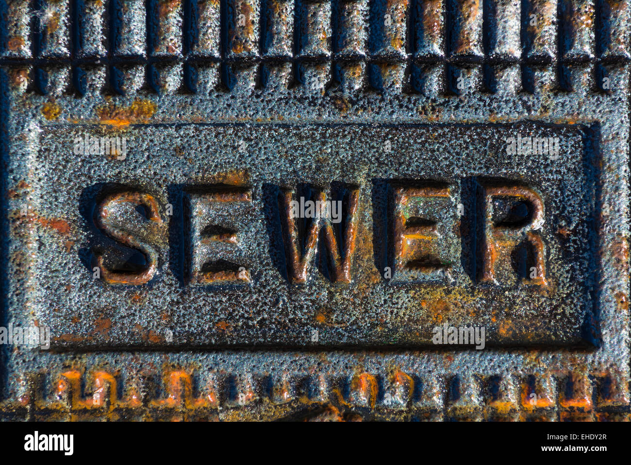 A sewer access cover with rusty iron printing - Stock Image