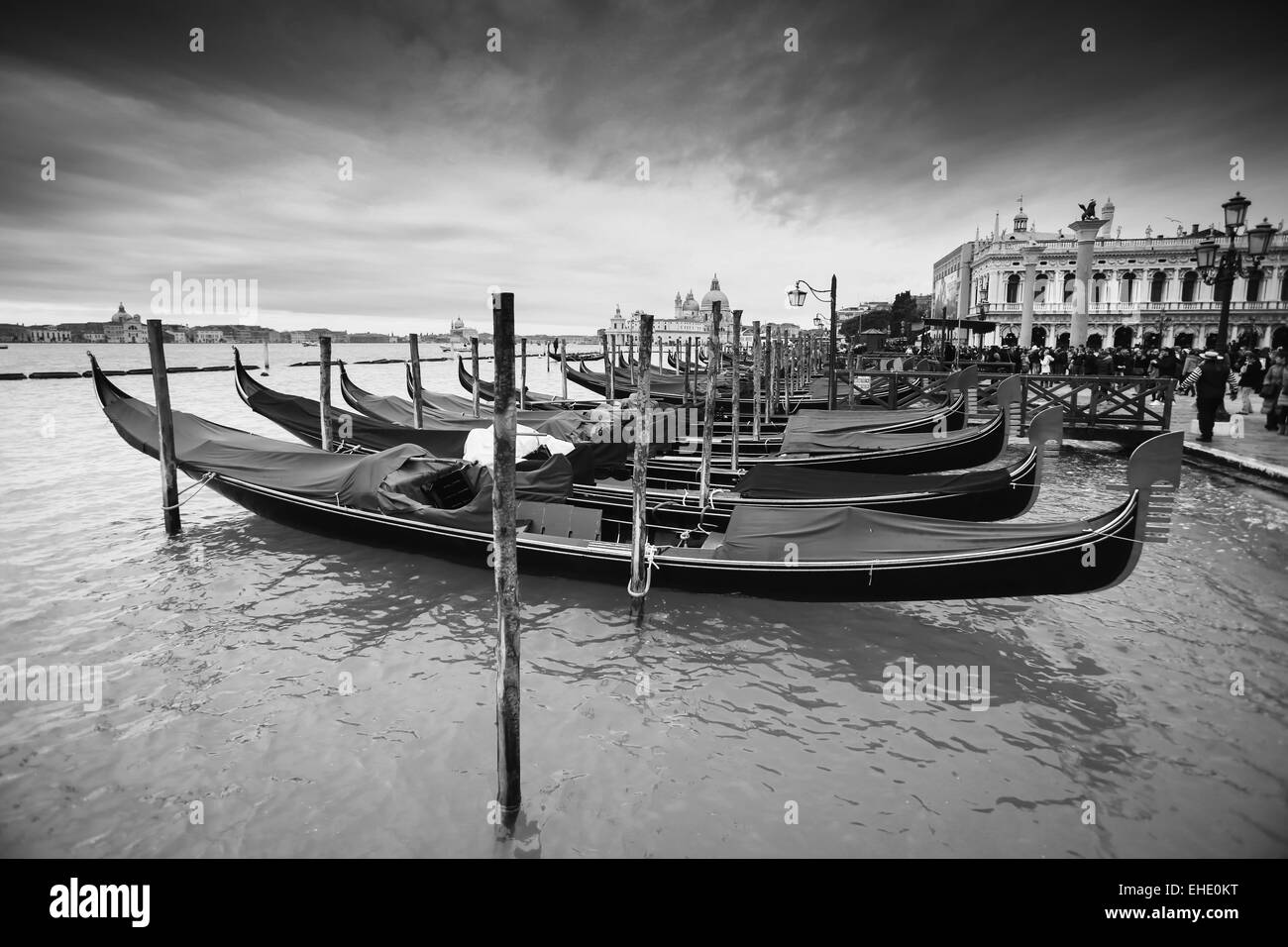 Gondolas moored in the water canal in front of people walking on Riva degli Schiavoni in Venice, Italy. - Stock Image