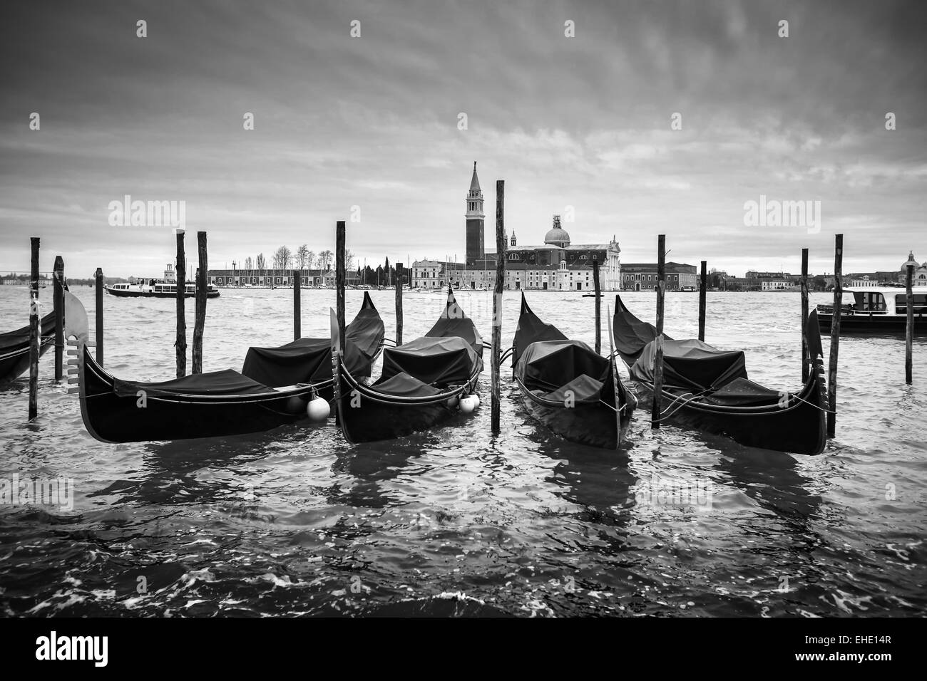 A view of the Church of San Giorgio Maggiore with gondolas parked in the water canal on Riva degli Schiavoni in - Stock Image
