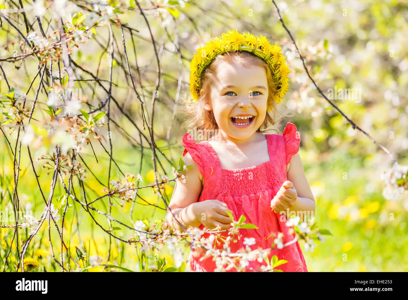 Happy little girl in spring sunny park - Stock Image