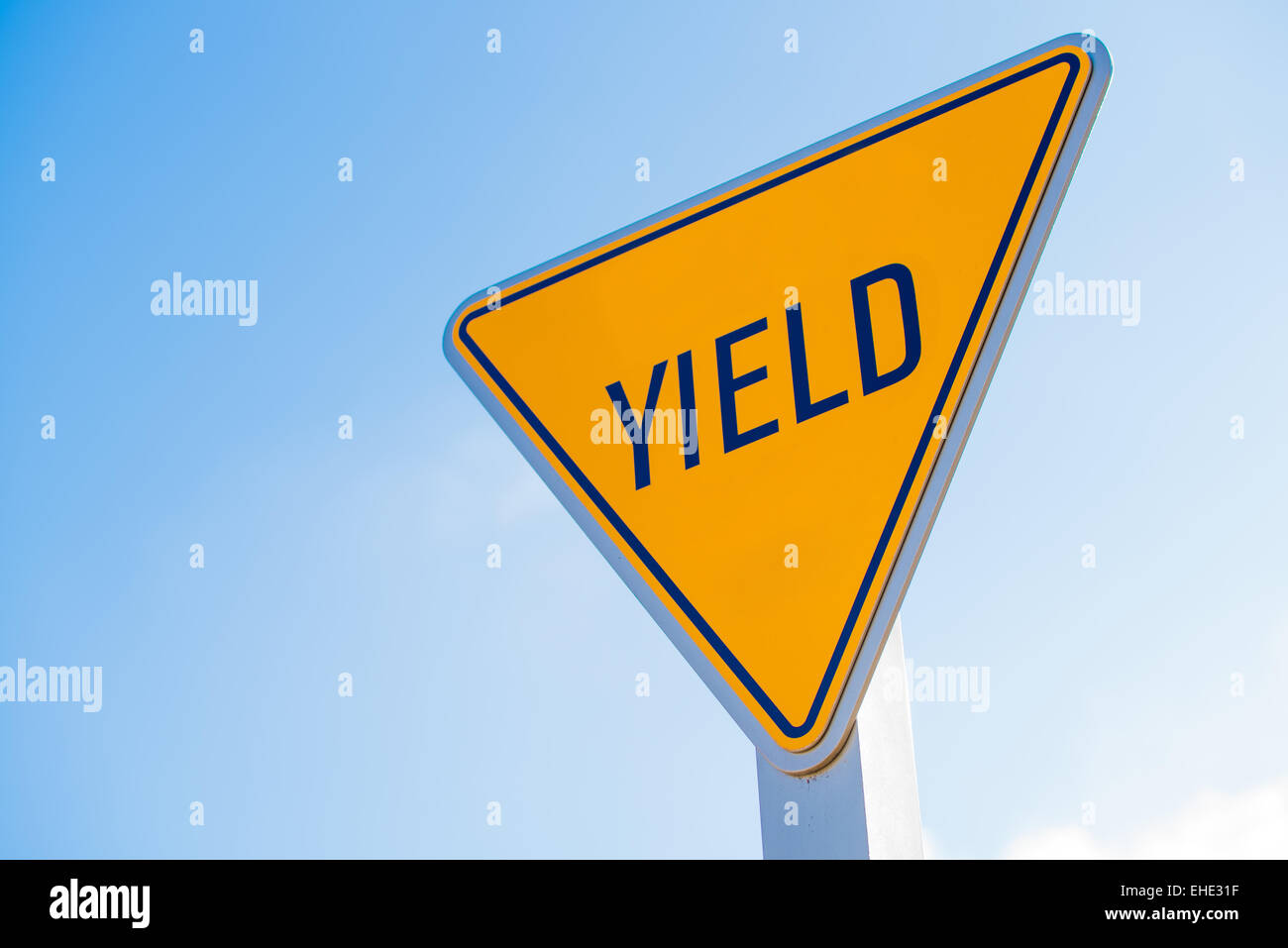 A yellow yield sign with a blue sky background - Stock Image