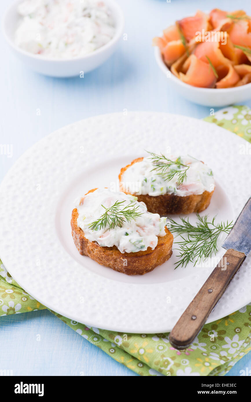 Canapes with soft cheese spread on white plate, selective focus - Stock Image