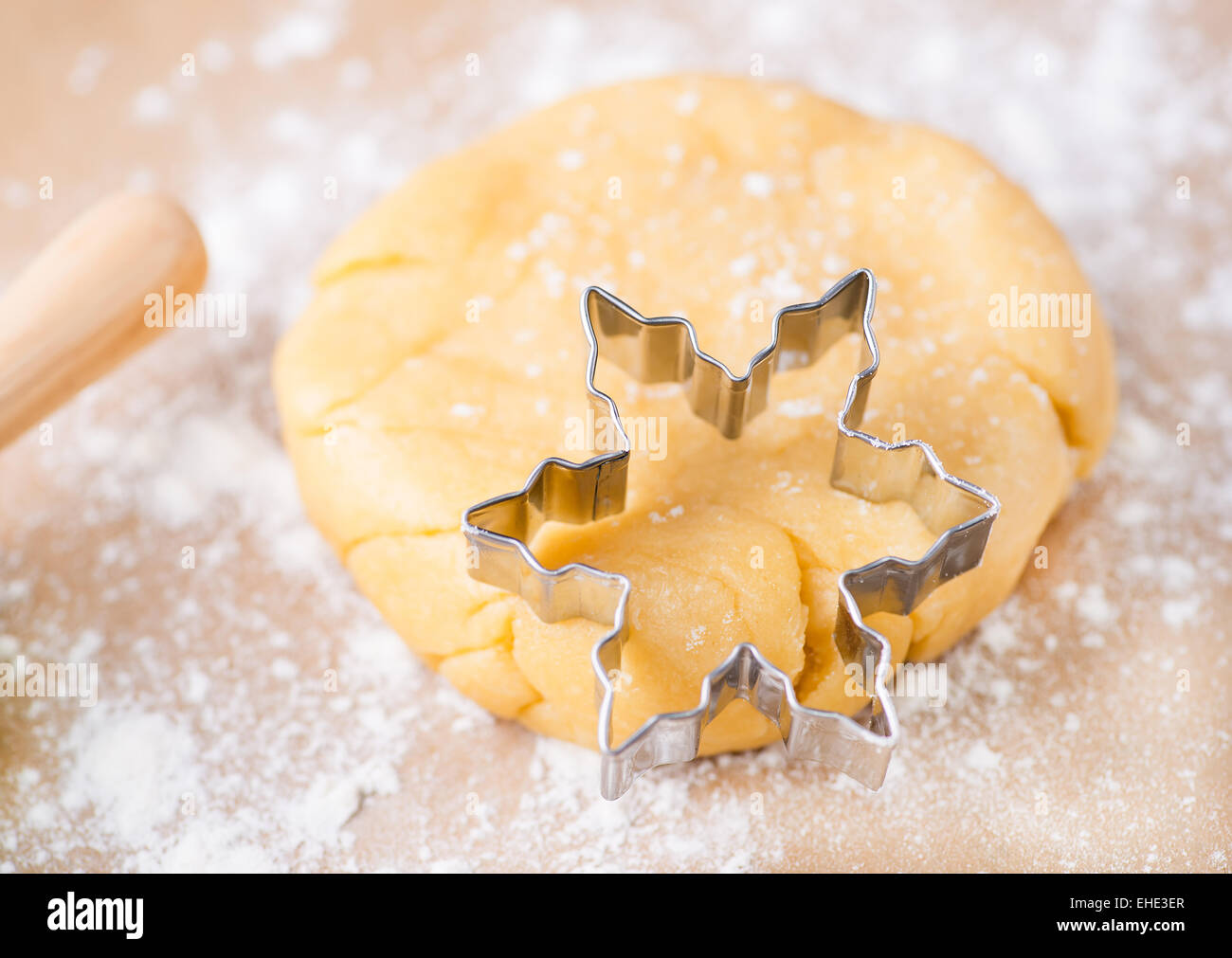 Shortcrust pastry dough with cookie cutter on a floured surface, selective focus - Stock Image