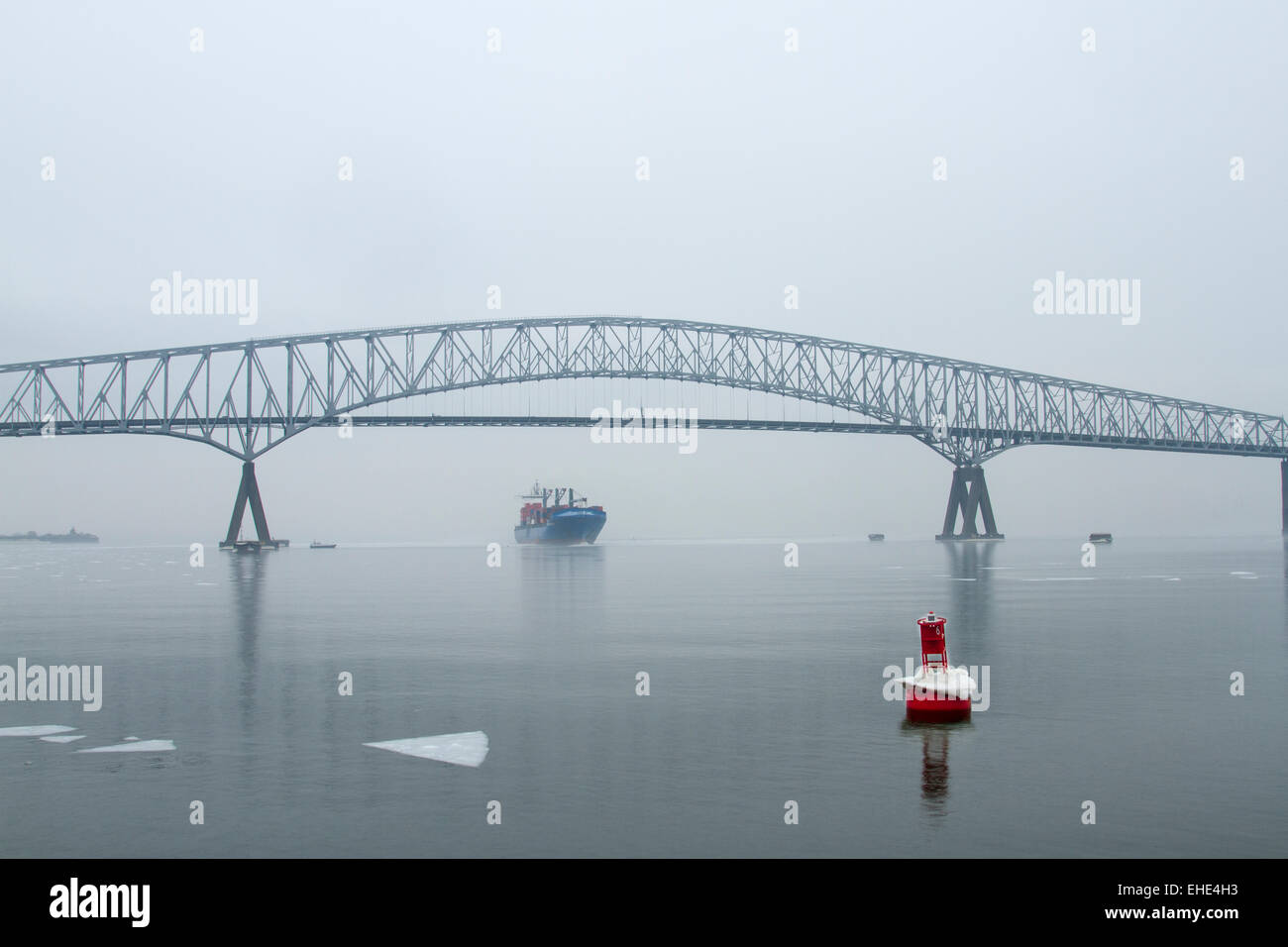 A Ship coming under the Francis Scott Key Bridge in Baltimore with ice in the harbor. Stock Photo