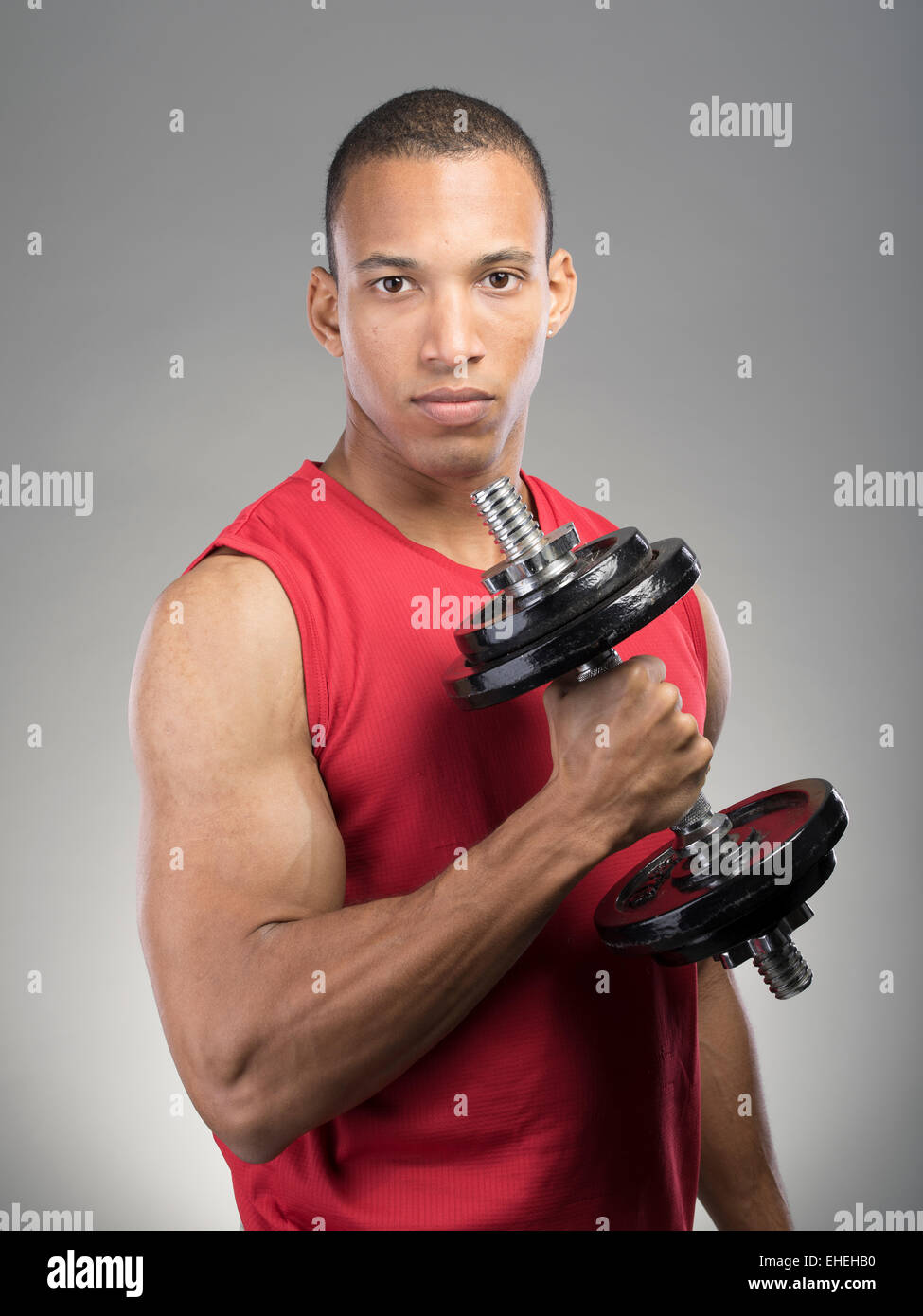Muscular man wearing red tank top vest using barbell - Stock Image