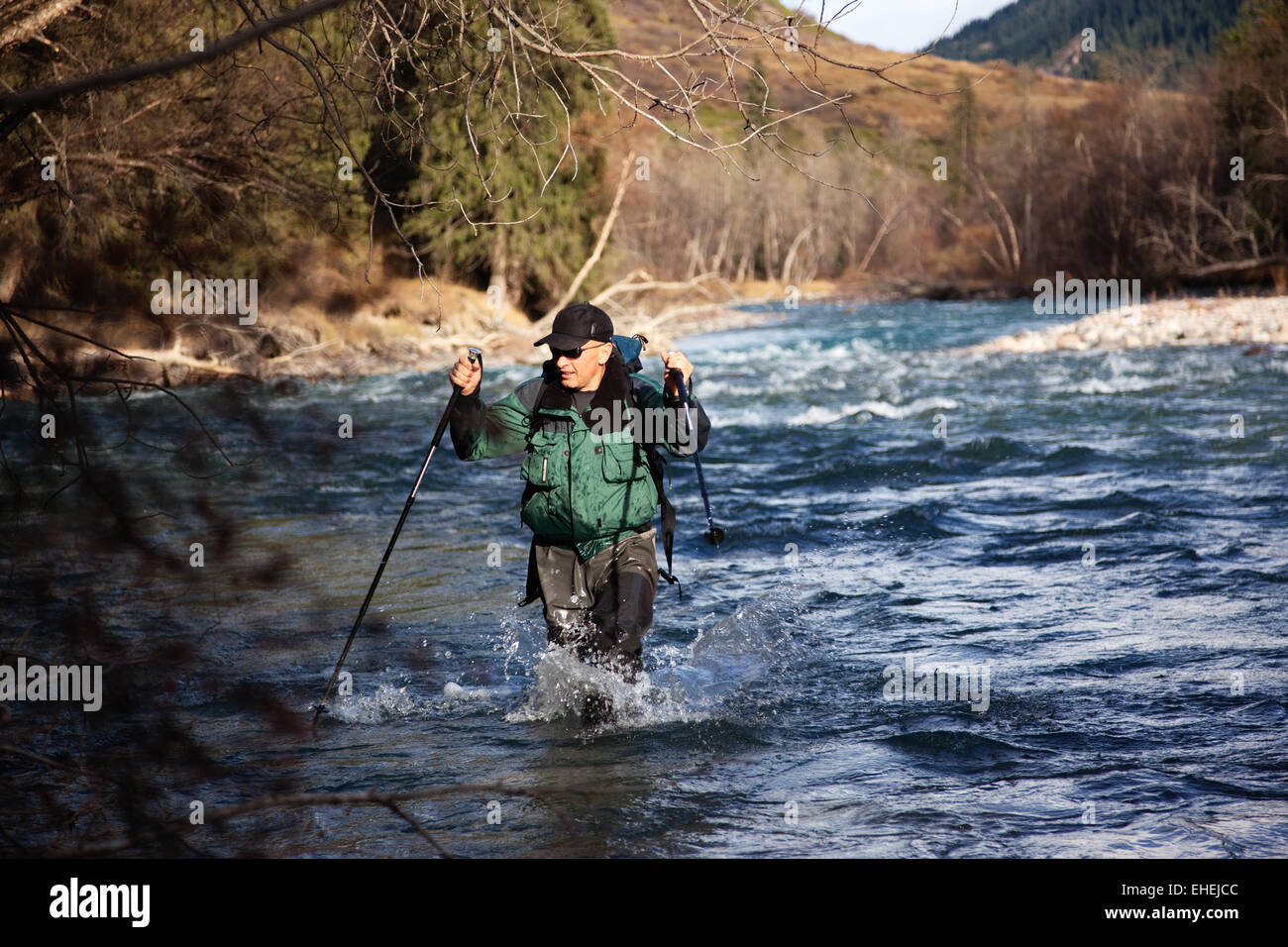Backpacker wade rugged river - Stock Image