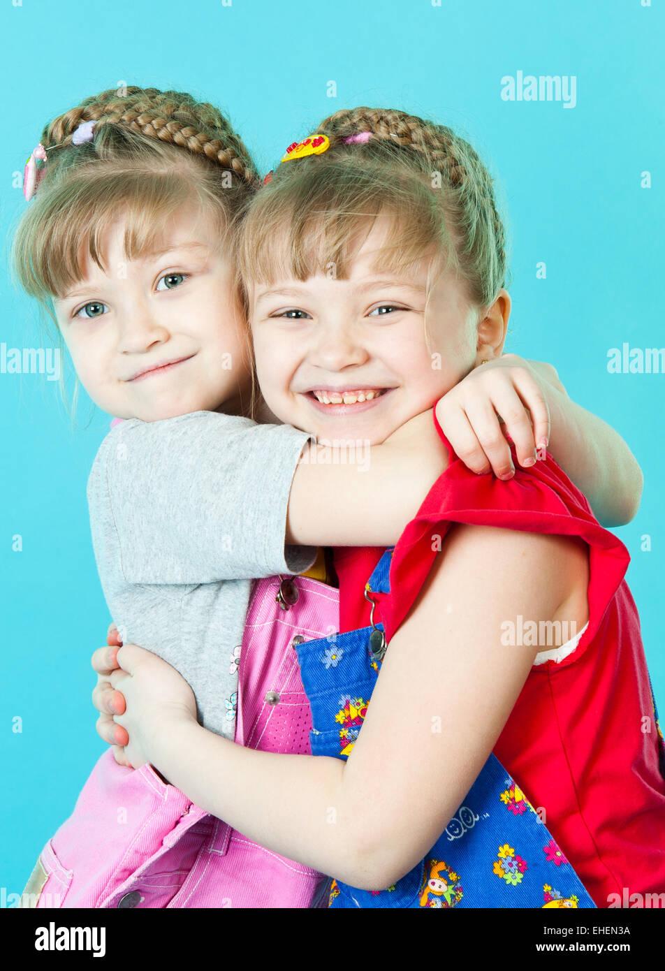 Twin sisters hugging Stock Photo