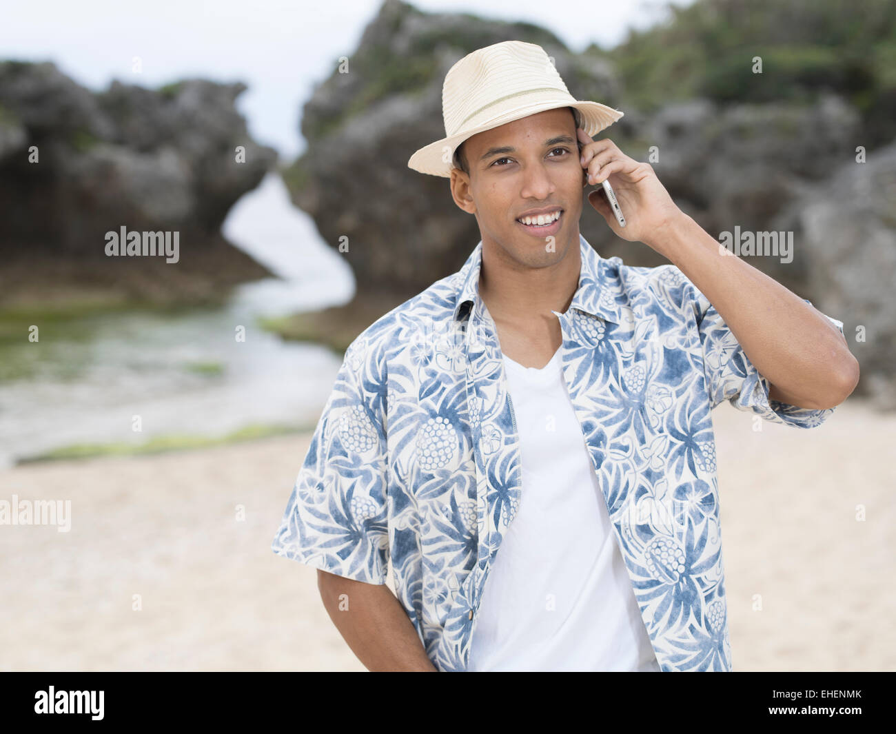 Man calling / telephoning with Apple iphone 6 smartphone while at the beach - Stock Image
